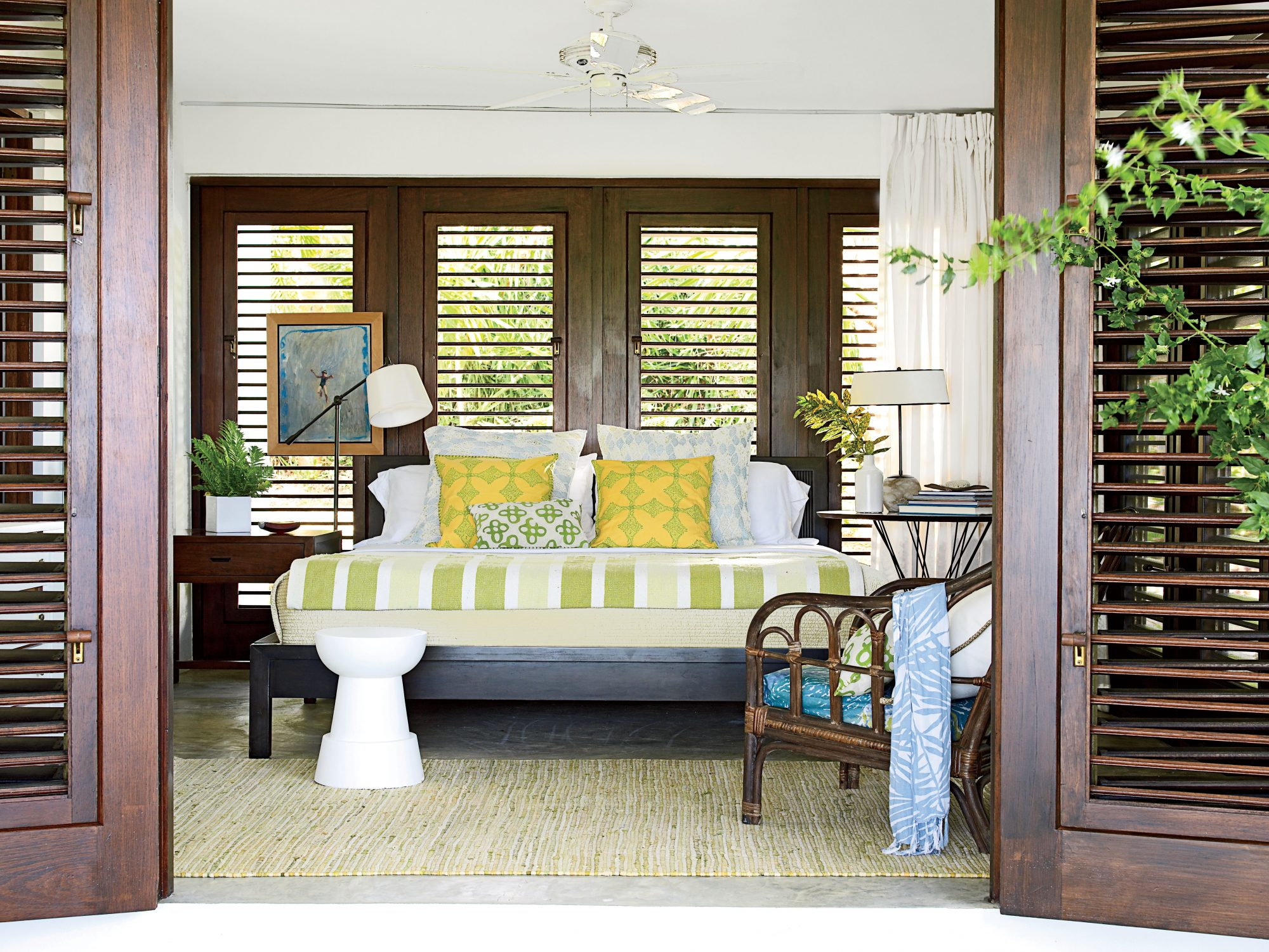 The fresh green and yellow linens in this guest bedroom on Vieques Island, Puerto Rico, along with the mahogany doors and windows, echo the lush landscape outside. Adding a small potted plant to the bedside table literally brings the outside in.