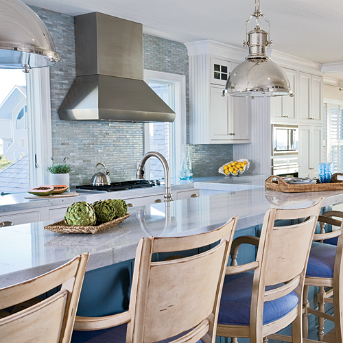 In this Delaware kitchen, ocean inspiration is everywhere, from the polished-nickel light fixtures that reflect the sunlight, to the swirls in the Blue Celeste marble countertops that echo the ocean current, and an ethereal, blue-green iridescent backspla