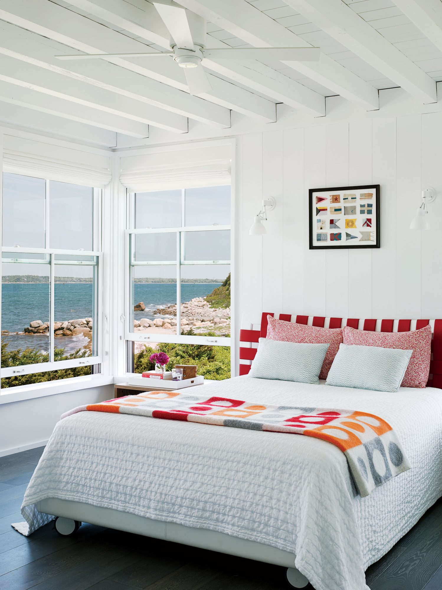 The owners of this Cape Cod cottage made their shoreline view the focus of this bedroom by cladding walls and ceilings in soft white paint that seems to amplify the natural light.