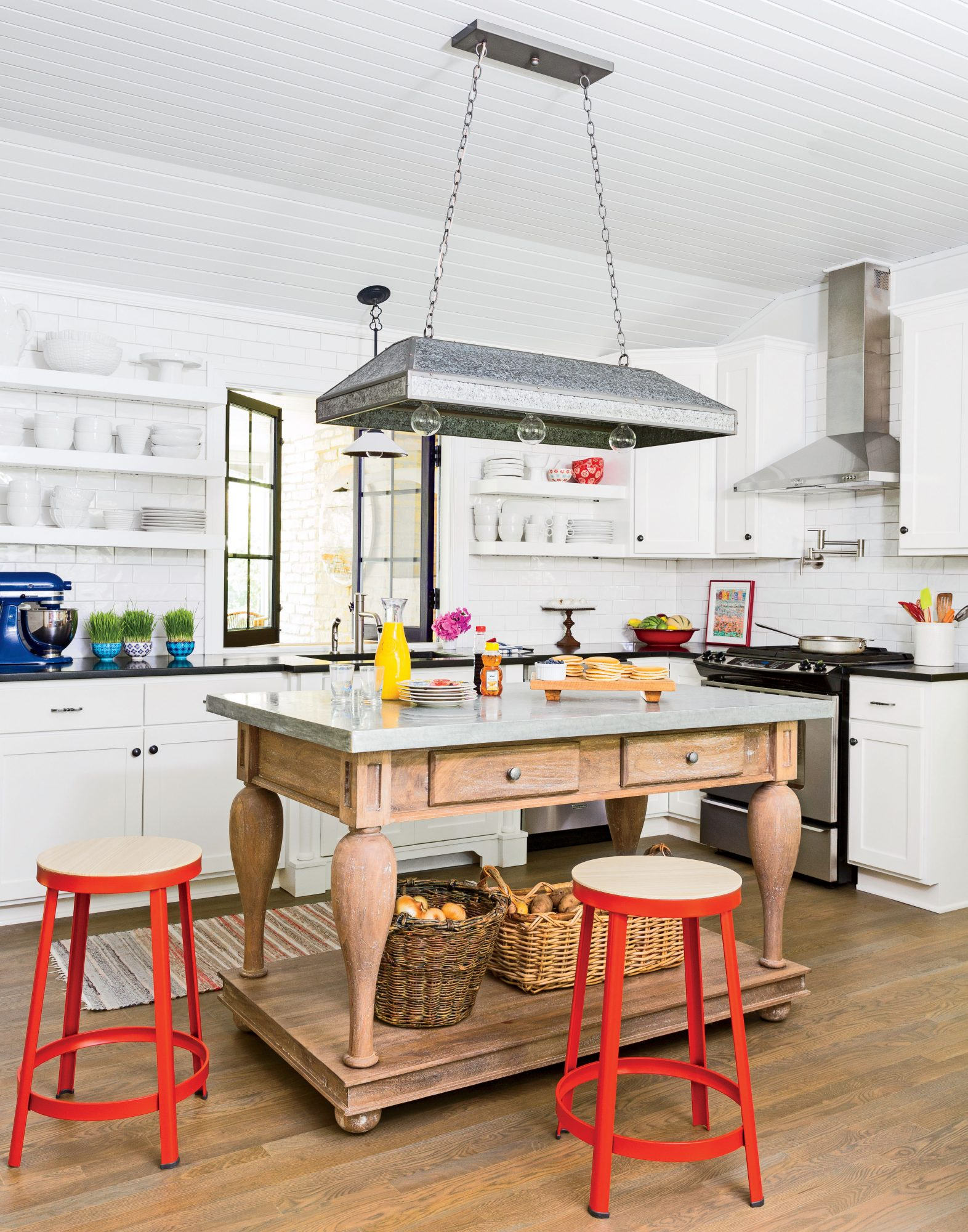 An all-white kitchen plays contrast to this Saugatuck, Michigan, cottage's surrounding, colorful rooms. Pops of primary colors—red stools and a blue stand mixer—add interest.