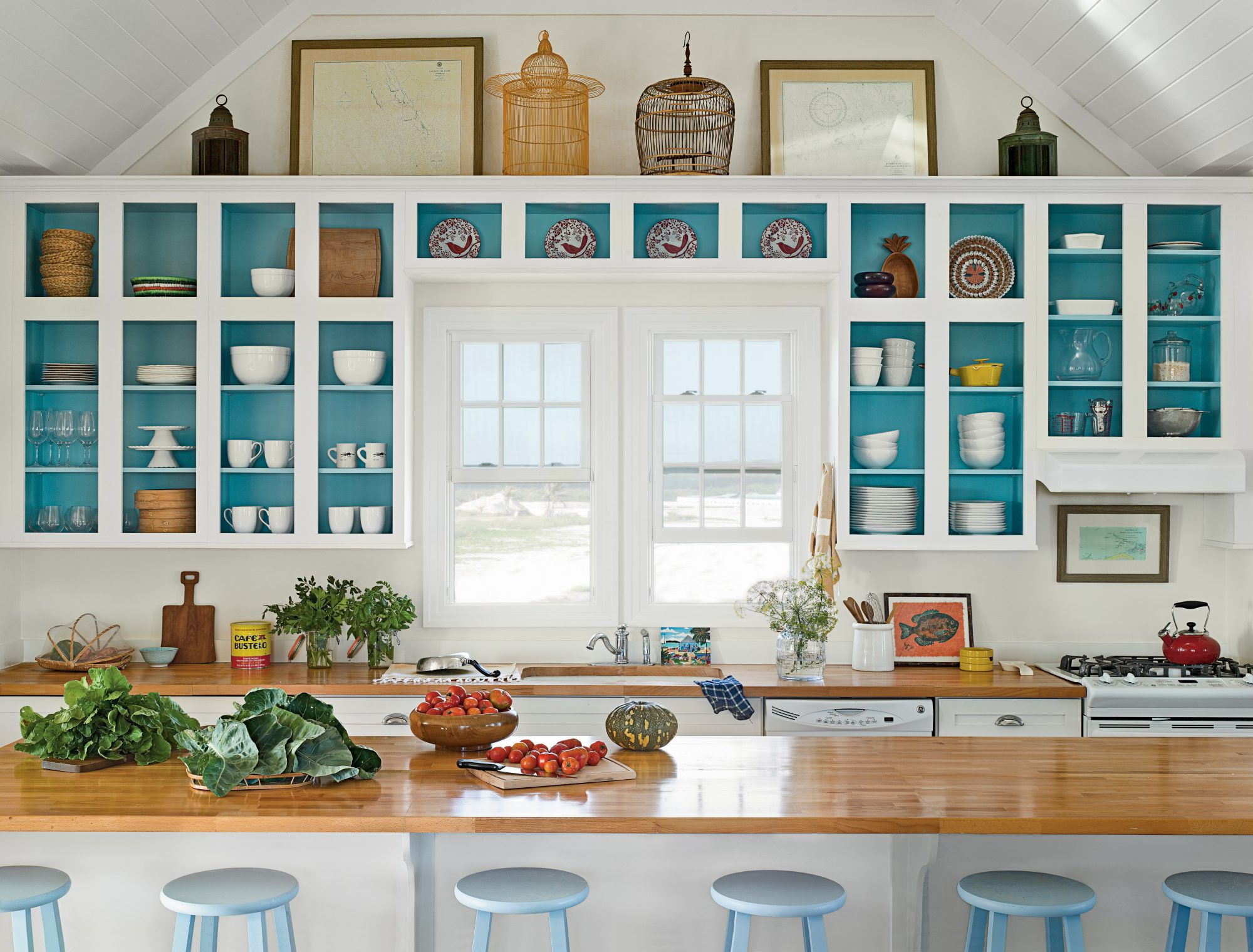 "This Abaco, Bahamas, kitchen feels like a vacation. Starting with the view (white sand, palm trees, and blue sky), the space has ""island getaway"" written all over it. The open cabinets are painted teal, making white dishes pop (and easy for guests to find"