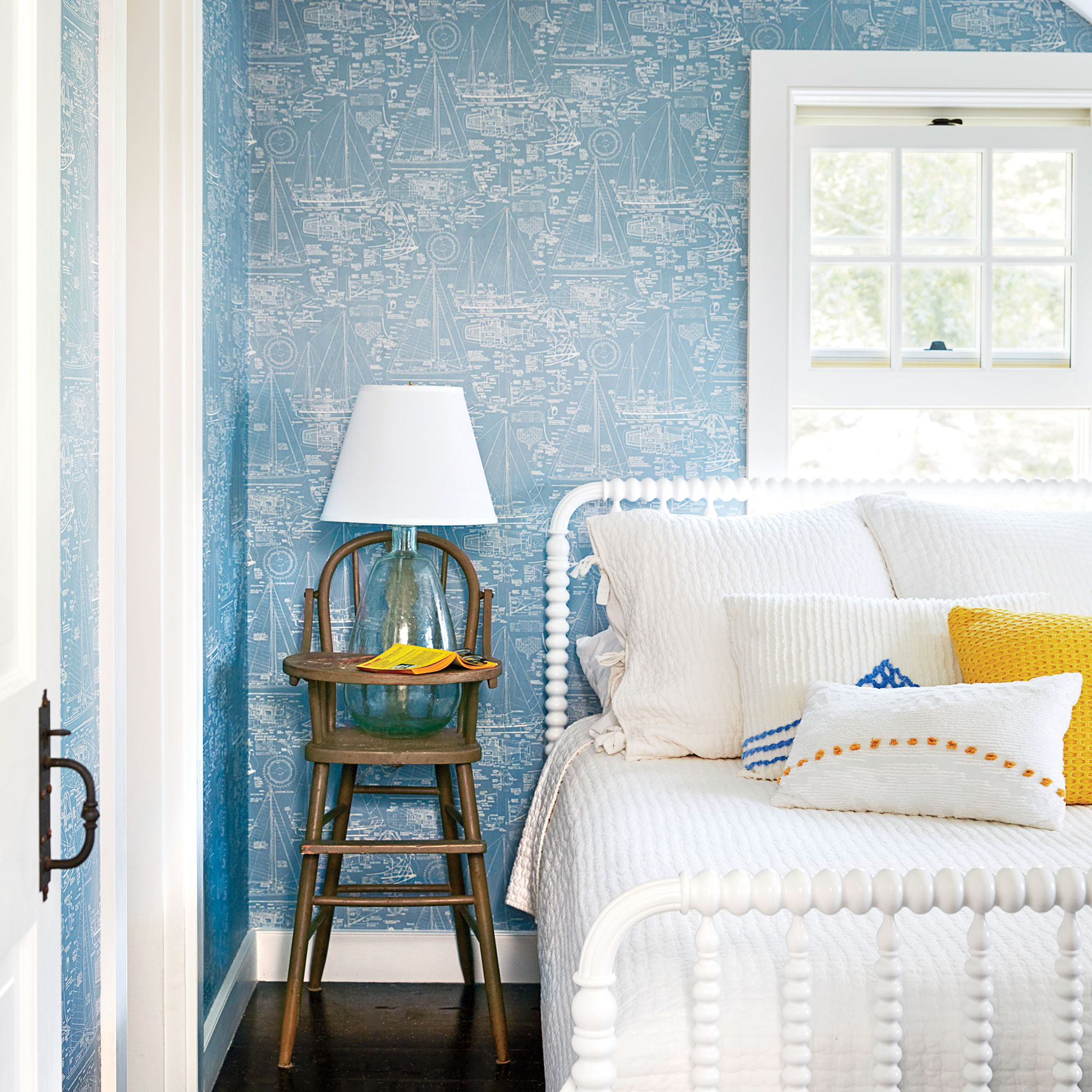 """This soft, vintage-inspired bedroom is a """"graceful reminder of the home's history,"""" says designer Alys Protzman, who brought the historic Cape Cod cottage back to life with bold pops of yellow in nearly every space. In this bedroom however, the signature"""