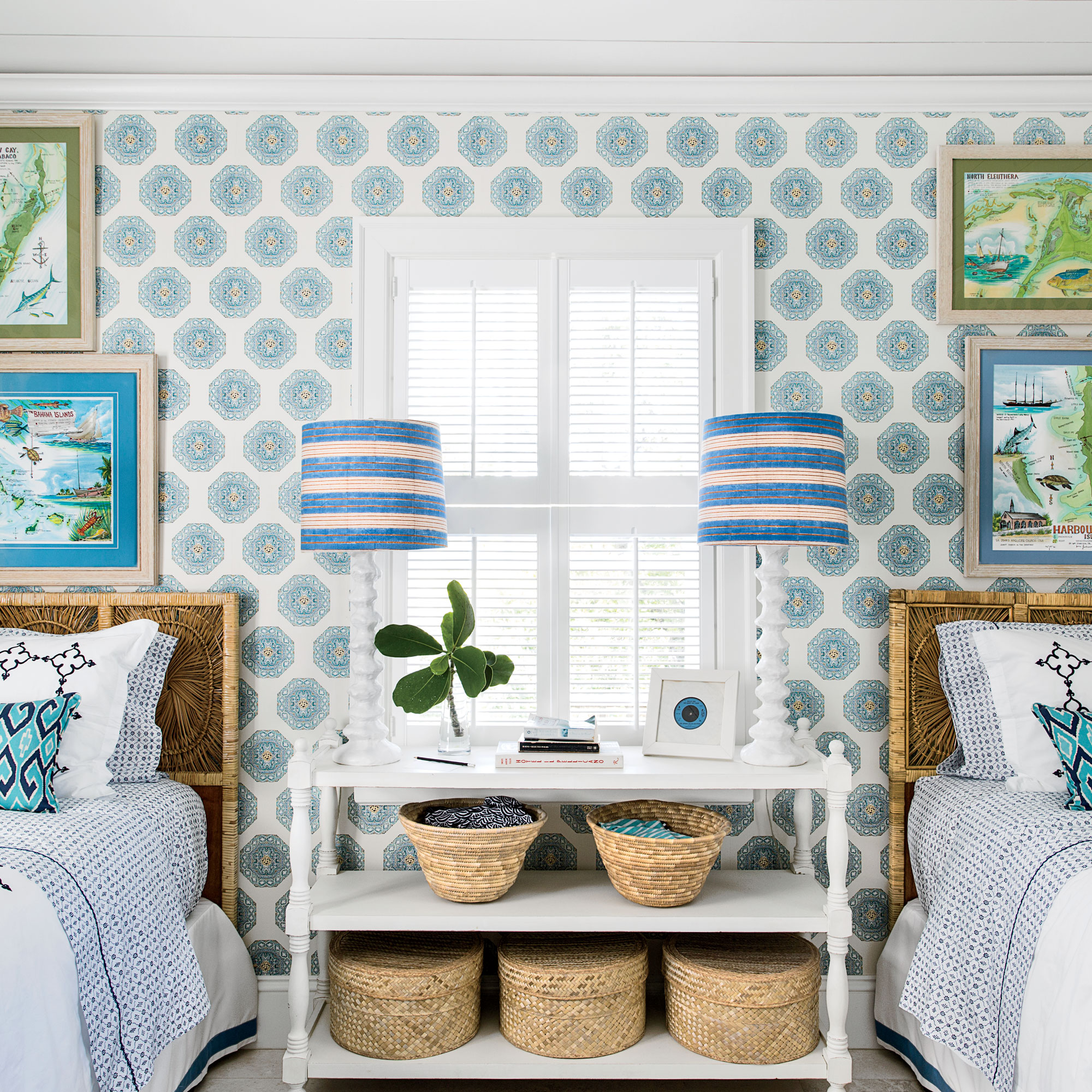"""""""Charming wallpaper gives a room a special, tucked-away feel,"""" says designer Amanda Lindroff, who applied a blue medallion print to the walls of this Harbour Island guest bedroom. Watercolors of Elbow Cay, Eleuthera, and Harbour Island are framed with mat"""