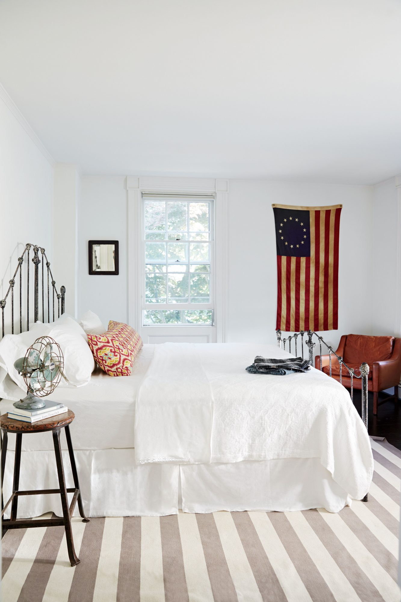 Combining treasures from local shops with crisp bedding and a nautically leaning rug give this Long Island bedroom a balanced and relaxed feel.
