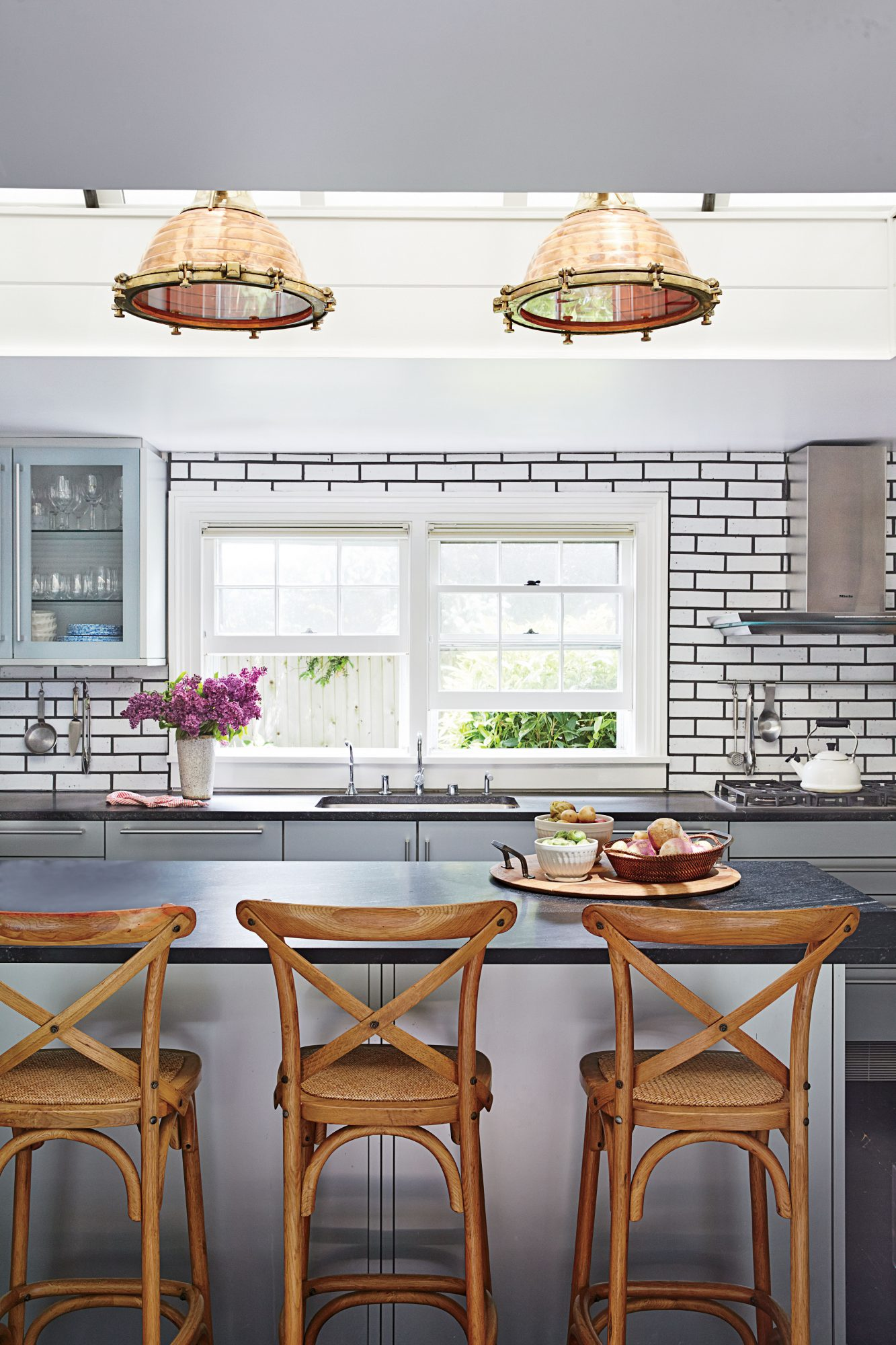Predominately outfitted with light and dark elements, this Long Island kitchen gets an infusion of natural elements from the copper light fixtures and wooden bar stools.