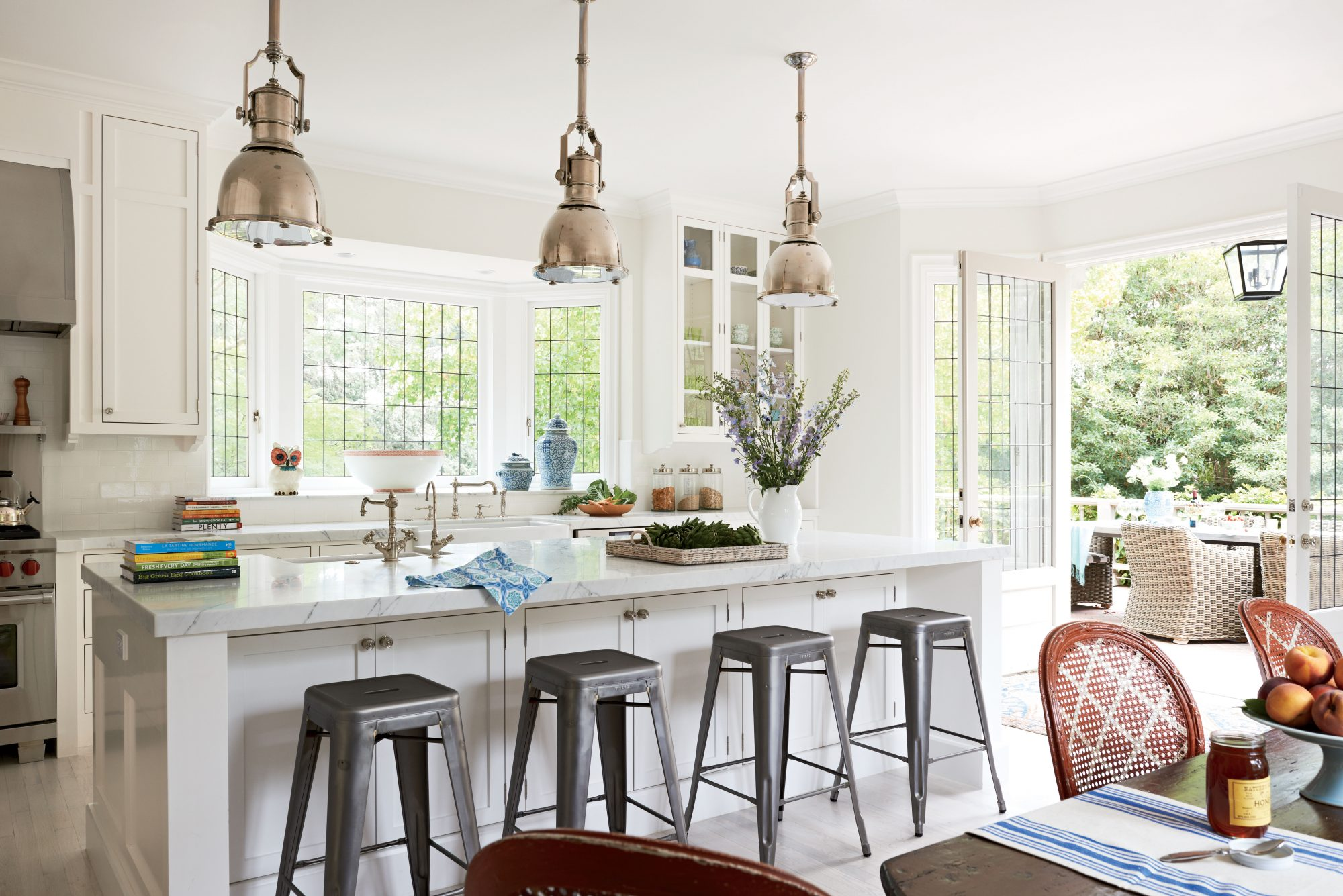 "This Montecito, California, kitchen ""has a great sense of symmetry and order, which lends itself well to frequent entertaining,"" says interior designer Melissa Warner Rothblum. The adjoining outdoor dining and living area, accessible via a pair of French"