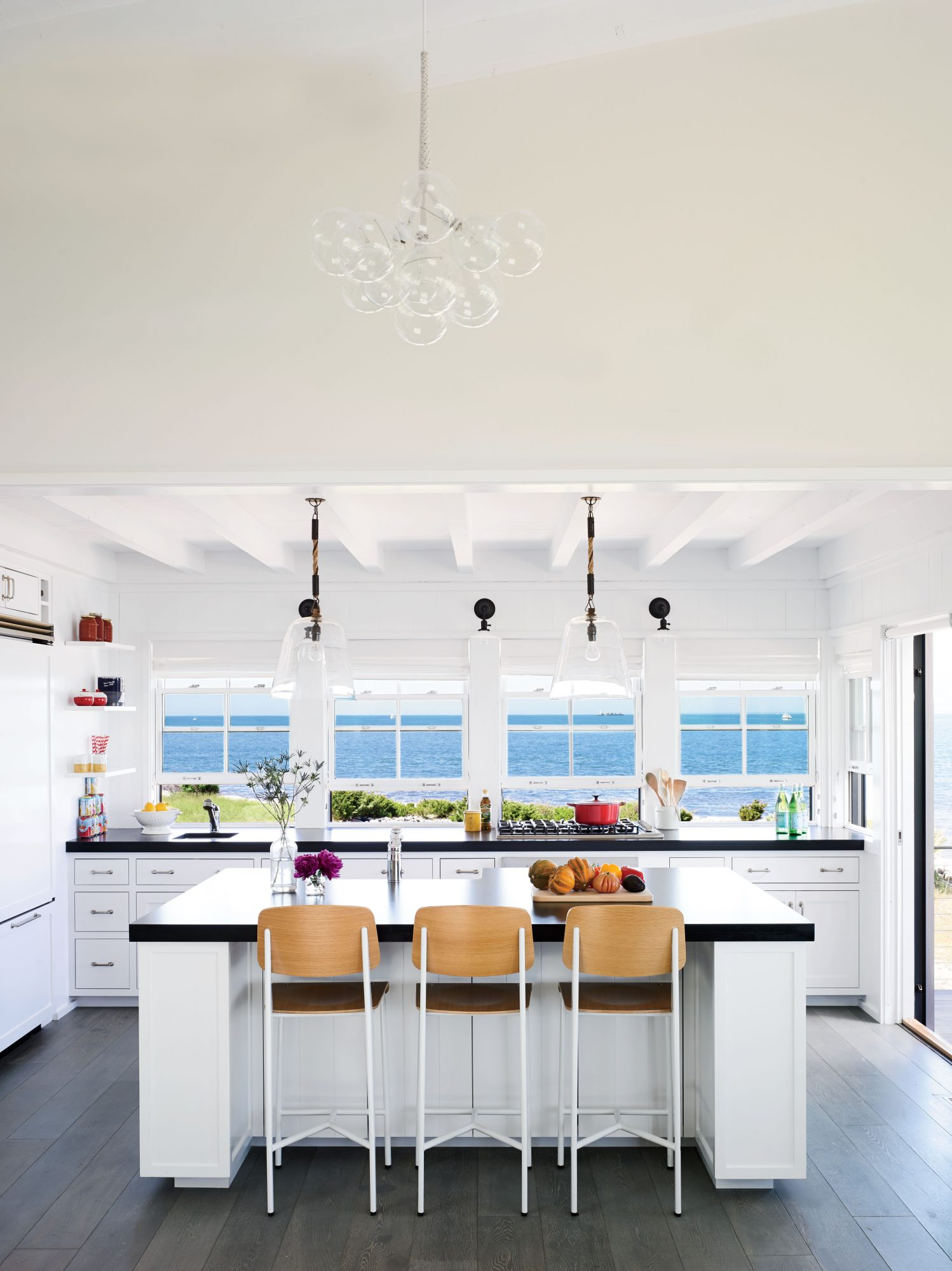 It's all about the ocean in this Buzzards Bay, Massachusetts, kitchen, and the mostly-white surfaces ensure that water and sky take center stage. Even the light fixtures, large, see-through glass pendants, were chosen with the vista in mind.