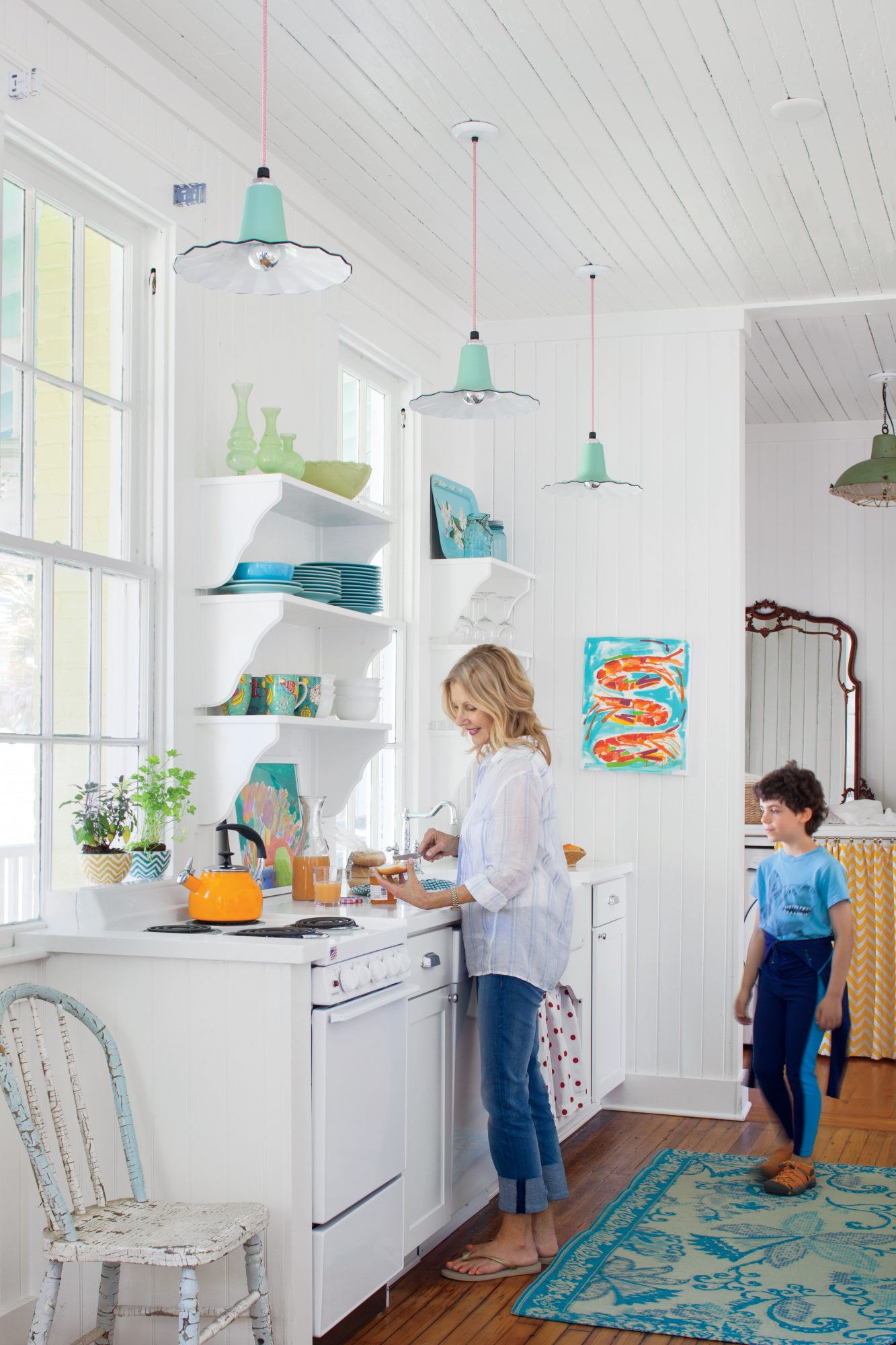 Water-hued plates, mugs, and vases match beautifully with mint green pendant lights in this small Tybee Island, Georgia, kitchen.