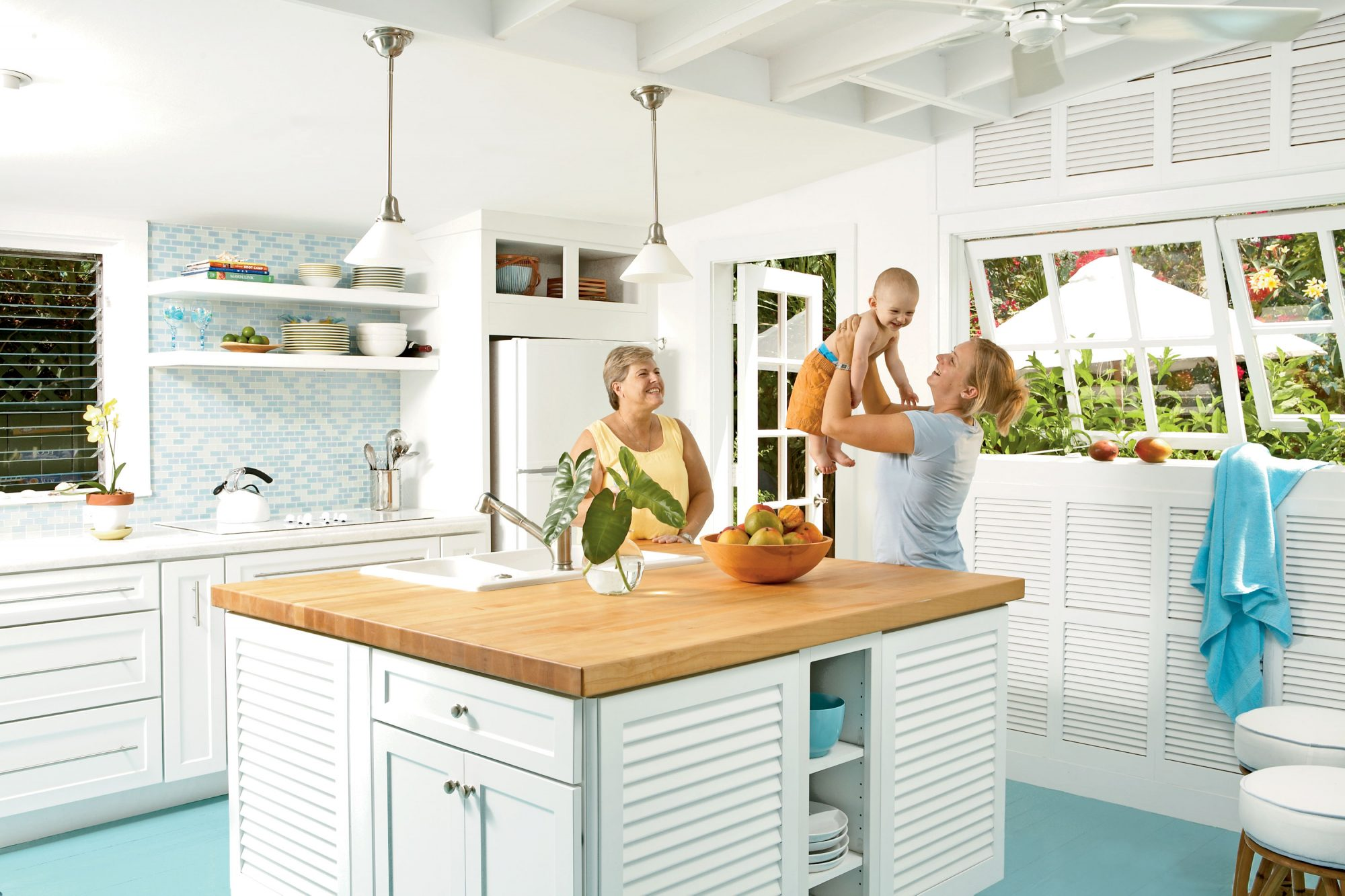 large butcher block island in this kitchen doubles as a multifunctional work space as storage is built beneath it