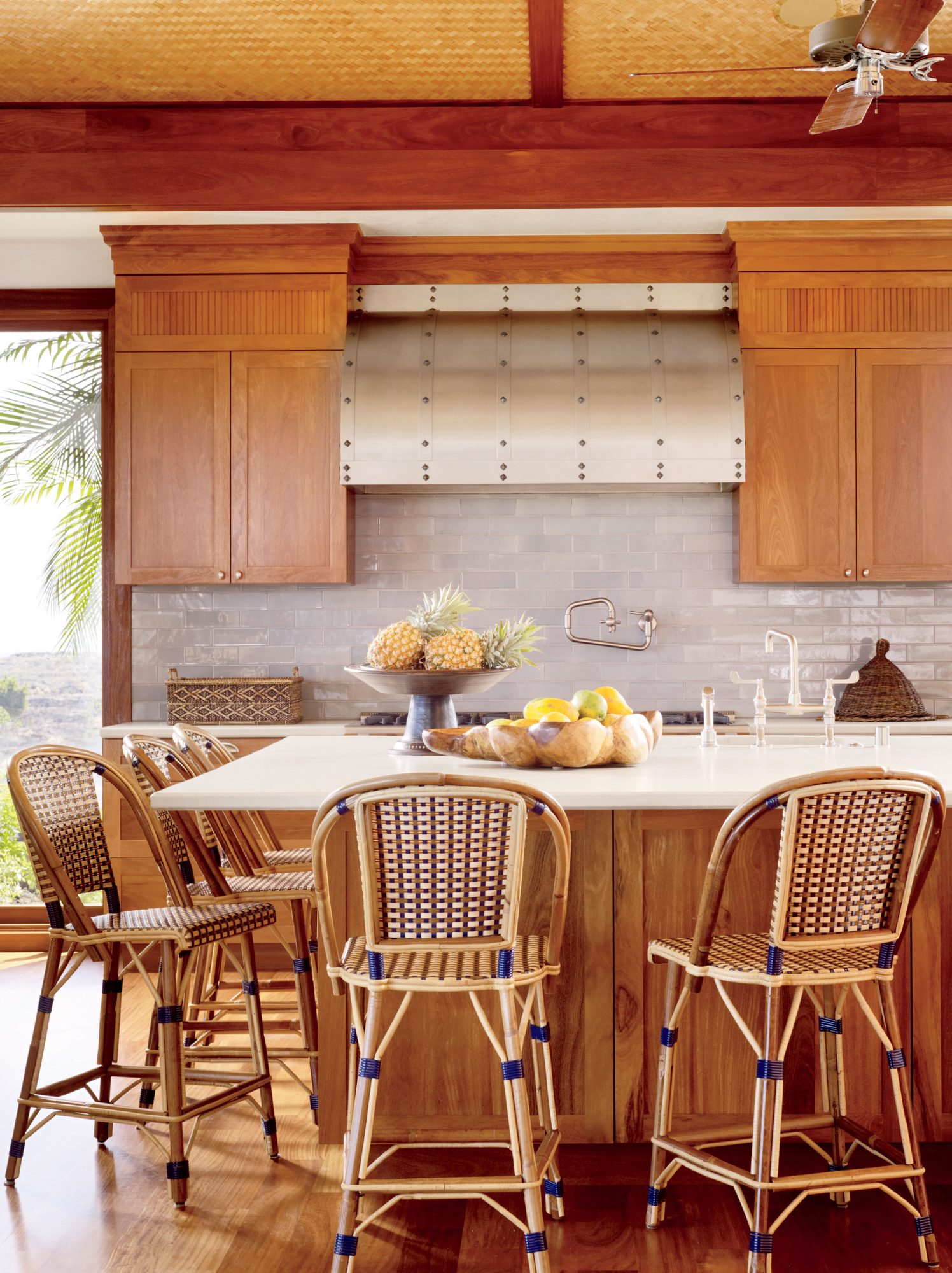This Kona, Hawaii, kitchen features honey-hued cabinets and woven barstools for a natural palette that allows the glimmering blue-gray tile backsplash to really shine.