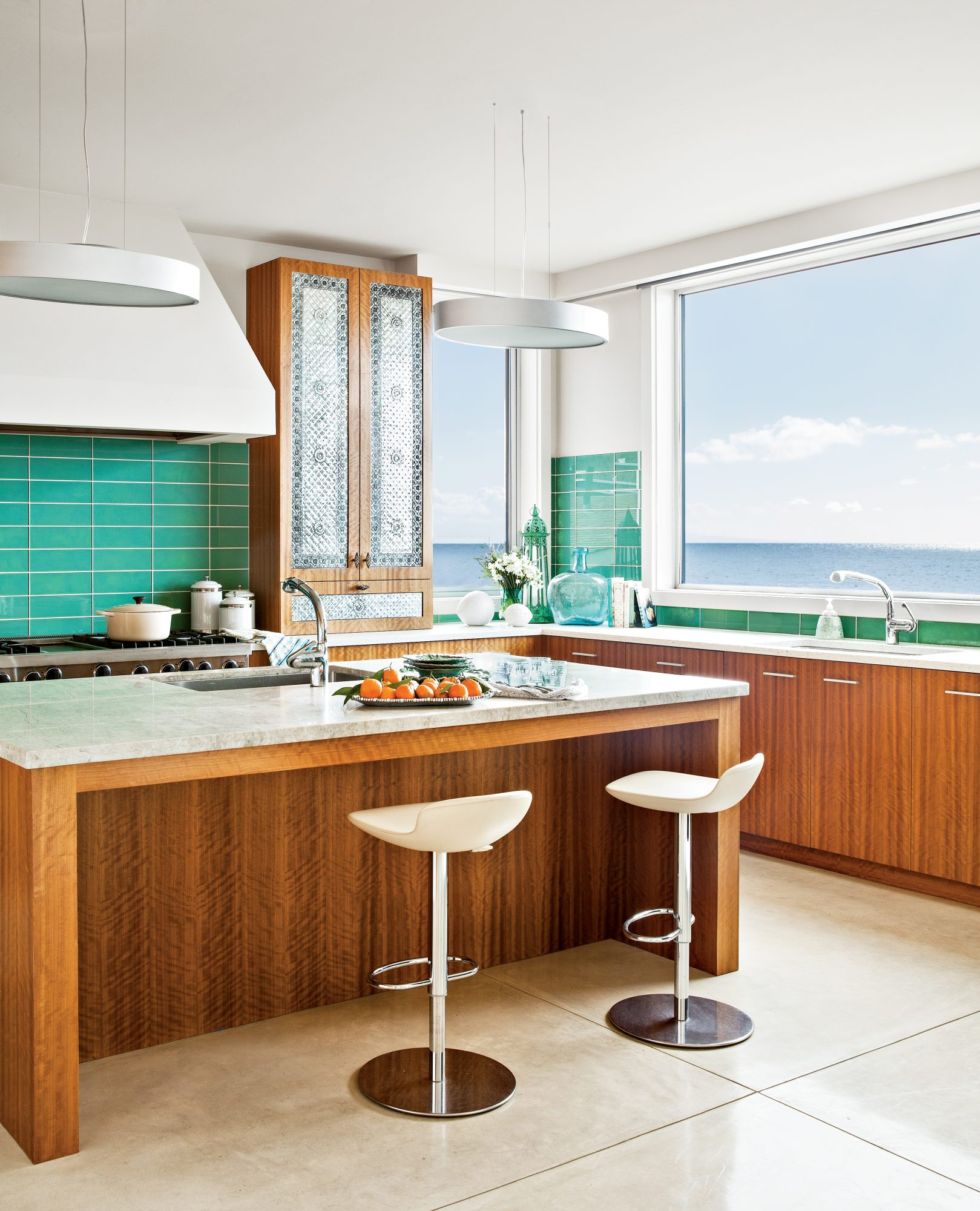 How do you hold your own against an ocean view this stellar? With warm, mod cabinets; bold, teal glass subway tile; and all-white everything else. A trio of punched metal cabinet doors give this kitchen an unexpected ornate touch, and the simple tile floo