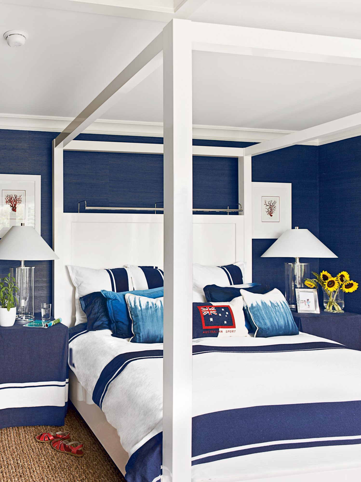 This two-tone bedroom in Hobe Sound, Florida, owned by Greg Norman and his interior designer wife, Kristen, is a sleek, nautical escape. Navy grasscloth wallpaper, slipcovered side tables, and striped bedding (plus fun dip-dyed accent pillows), make the r