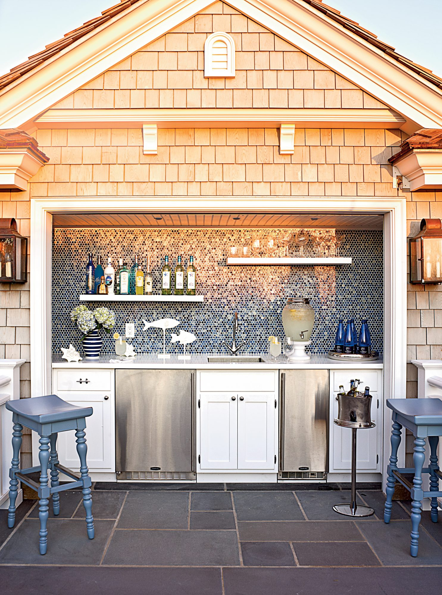 While this stunner isn't a full-blown kitchen per se, it is quite an impressive set-up for being out in the elements. With its shimmery tile backsplash, open shelving, mini fridge, wine fridge, and slate floor tiles, it's a no brainers of a hangout for a