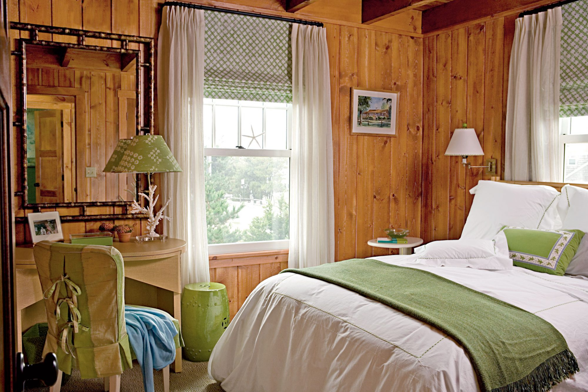 wood-paneled bedroom with accents of kiwi green used (in a blanket at the foot of the bed)