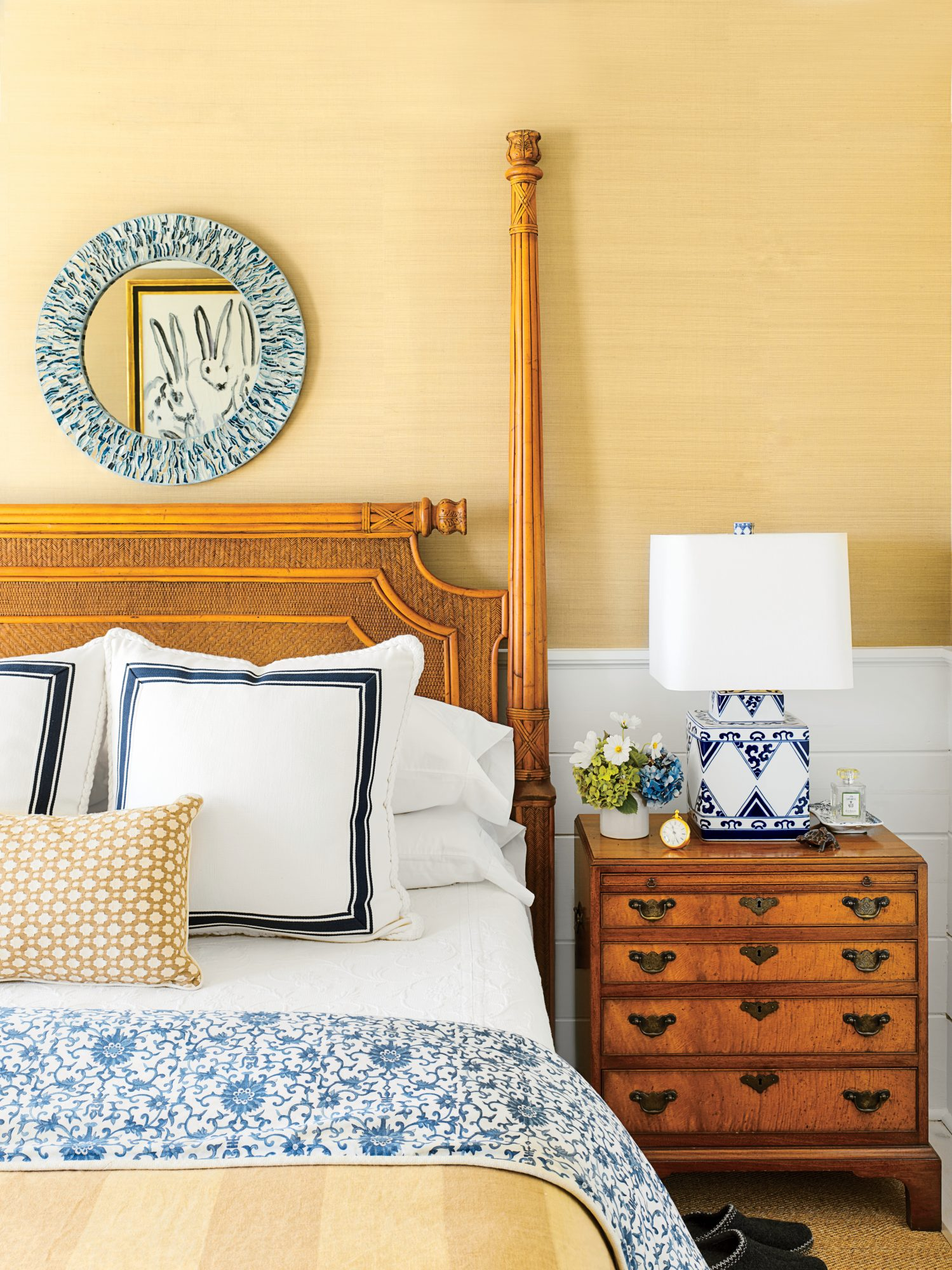 Honey tones set the stage in this serene Provincetown, Rhode Island, master bedroom. Above the Ficks Reed bed is a pretty, custom mosaic mirror in sea-going blues, which are echoed in the bedding and bedside table lamp.