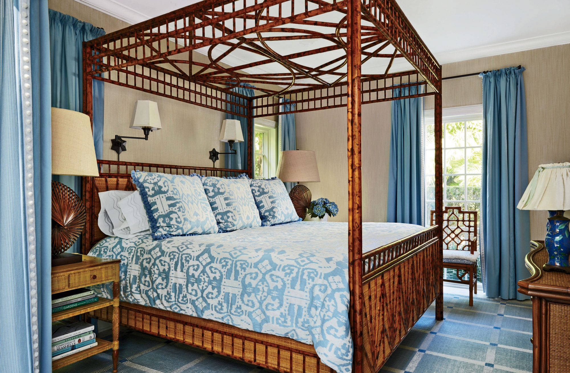 Because the wicker and bamboo bed frame almost reaches the ceiling, the designer of this Florida bedroom added two oversize nautilus lamps to keep the scale consistent.