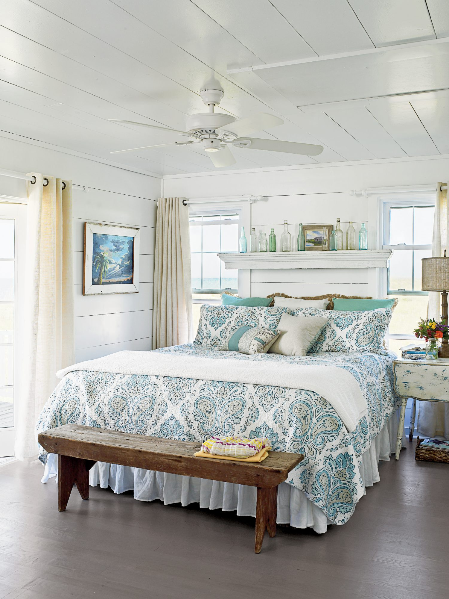 """A blue-and-green patterned duvet and accent pillows add a lively touch to the master bedroom in this Bald Head Island, North Carolina, cottage. """"I kept the decor simple but comfortable,"""" says designer and homeowner Tiffany McWhorter. """"I didn't want any on"""