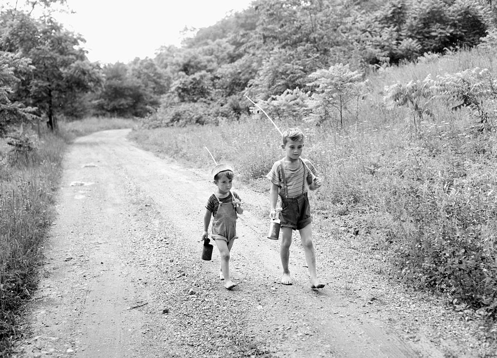 Two young boys head home after fishing, ca. 1950.