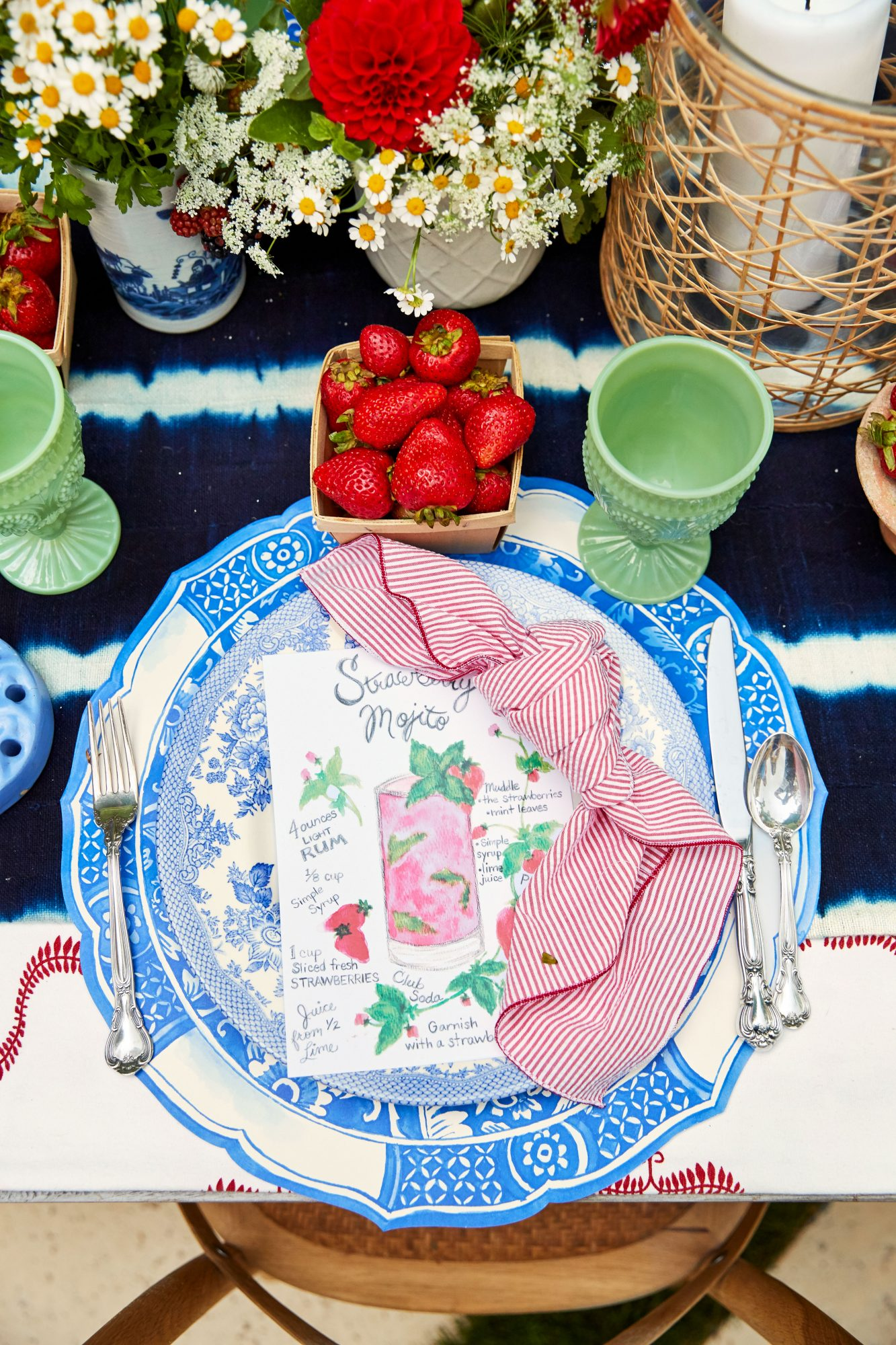 4th of July table setting with strawberries, red and white flowers, and blue paper placemats