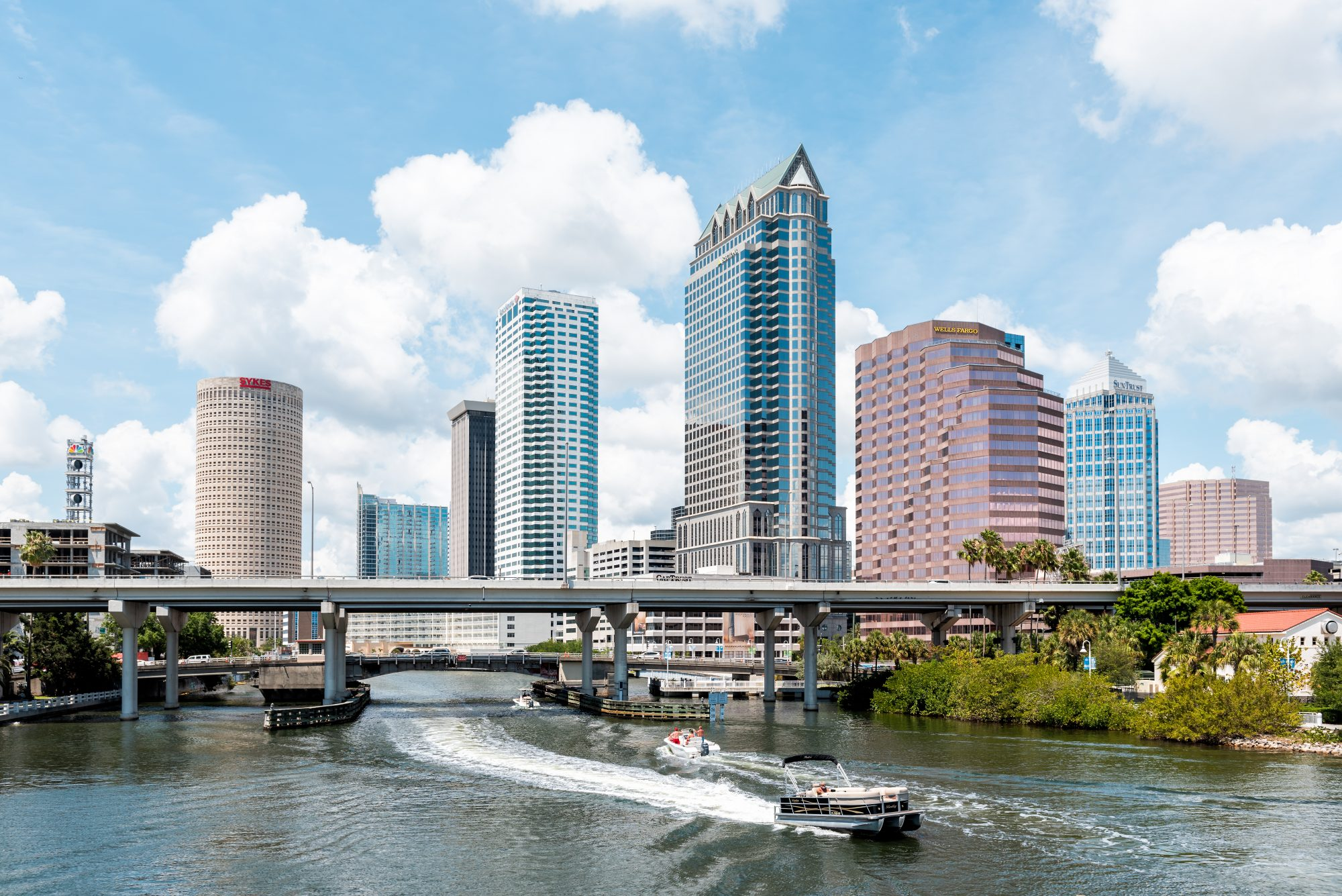 Tampa, USA - April 27, 2018: Downtown city in Florida with bridges, highway, boat yacht, skyscrapers office modern buildings cityscape with signs for Wells Fargo, NBC, Sykes