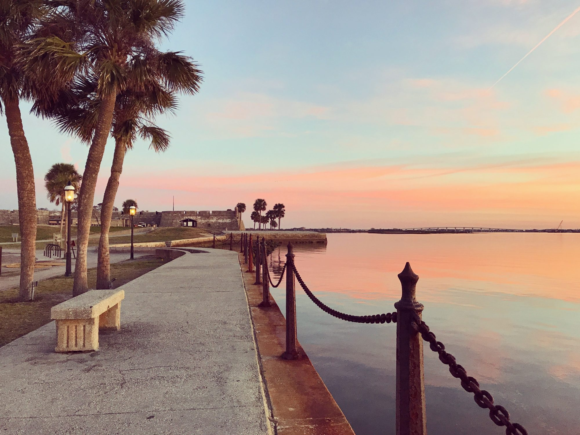 Palm trees and a sidewalk along the water's edge leading to the fort illuminated at dawn in St. Augustine. A beautiful and whimsical sunrise sky over the water. Swirling pink, yellow and orange clouds against a brilliant golden sky. Travel. Nature.