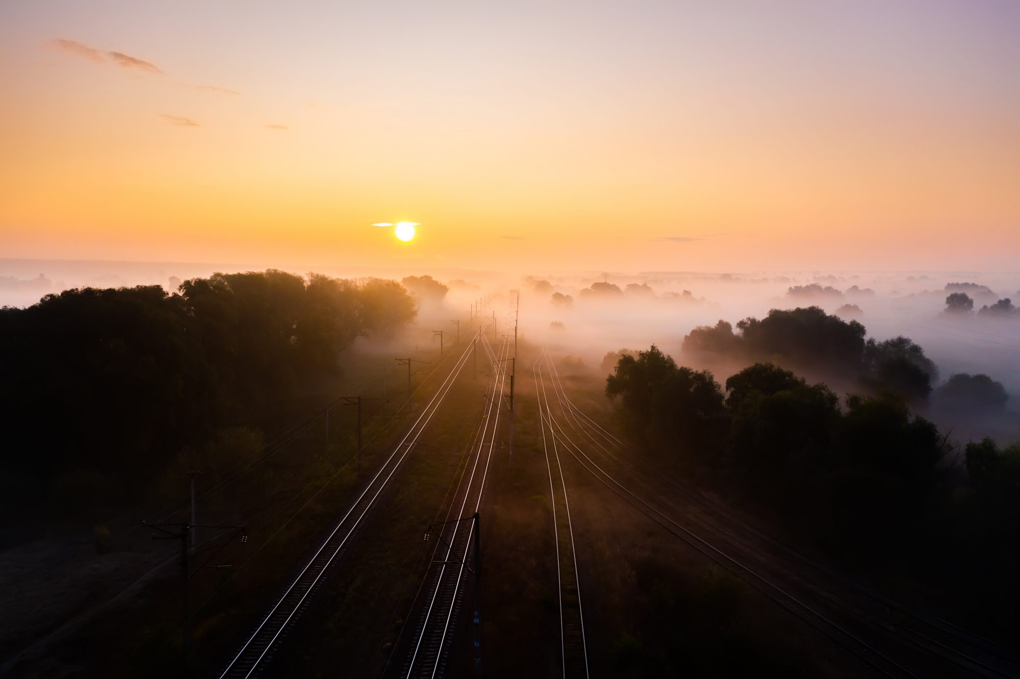 Railway track at sunrise in the fog. View from the drone.