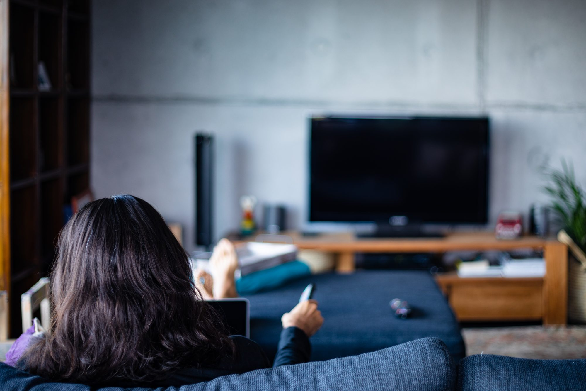 A man using laptop and watching TV using remote control