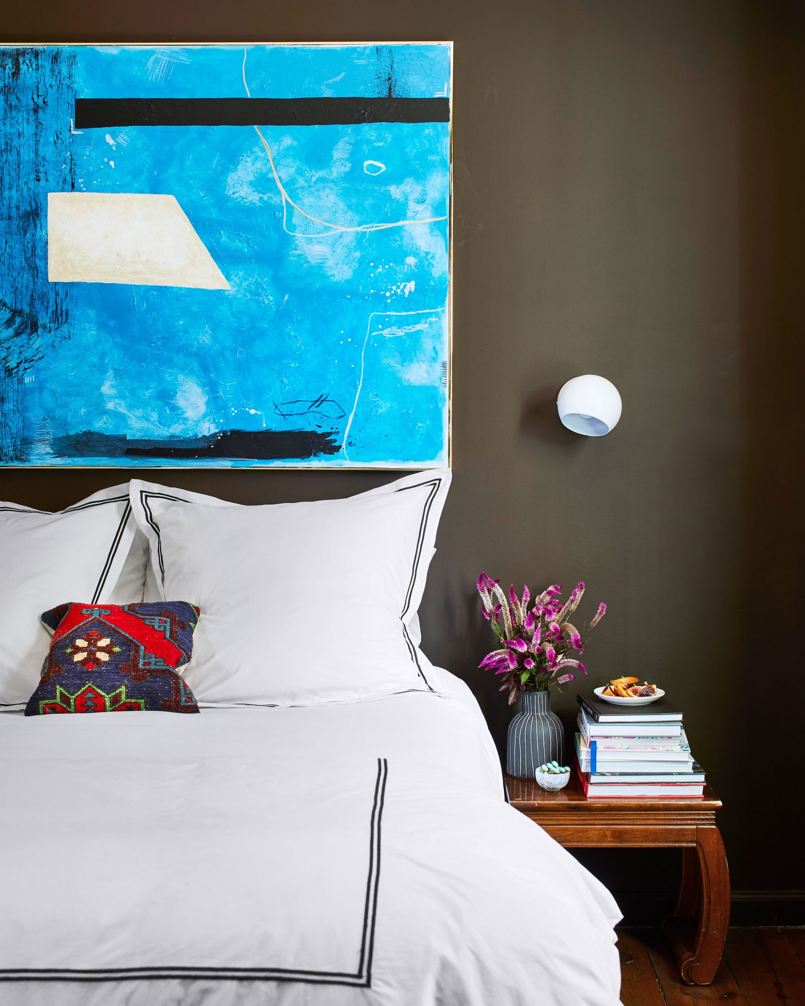 Alabama Cabin Guest Bedroom with Chocolate Brown Walls and Bold Blue Painting Above Bed