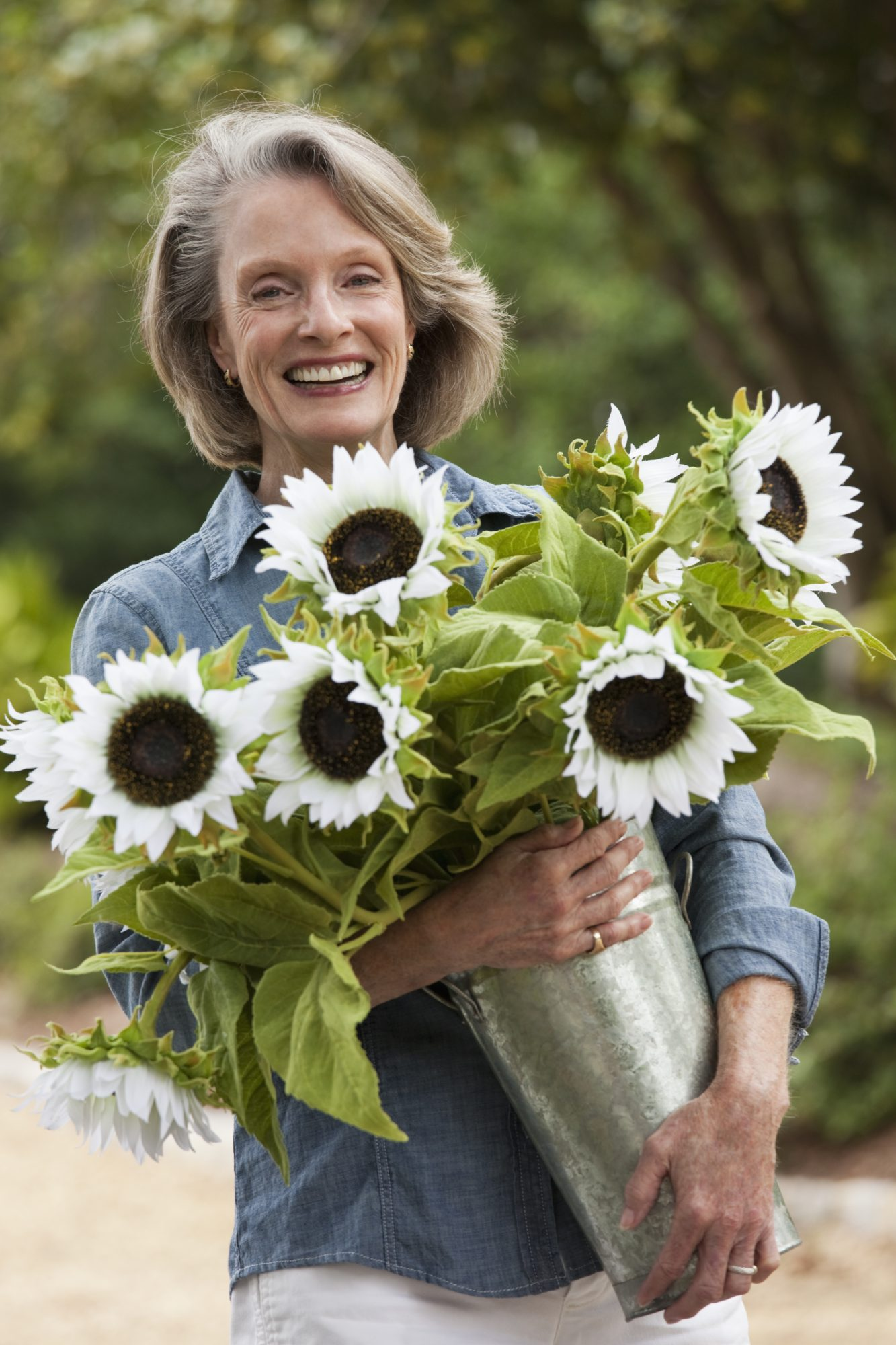 Caucasian woman carrying vase of sunflowers