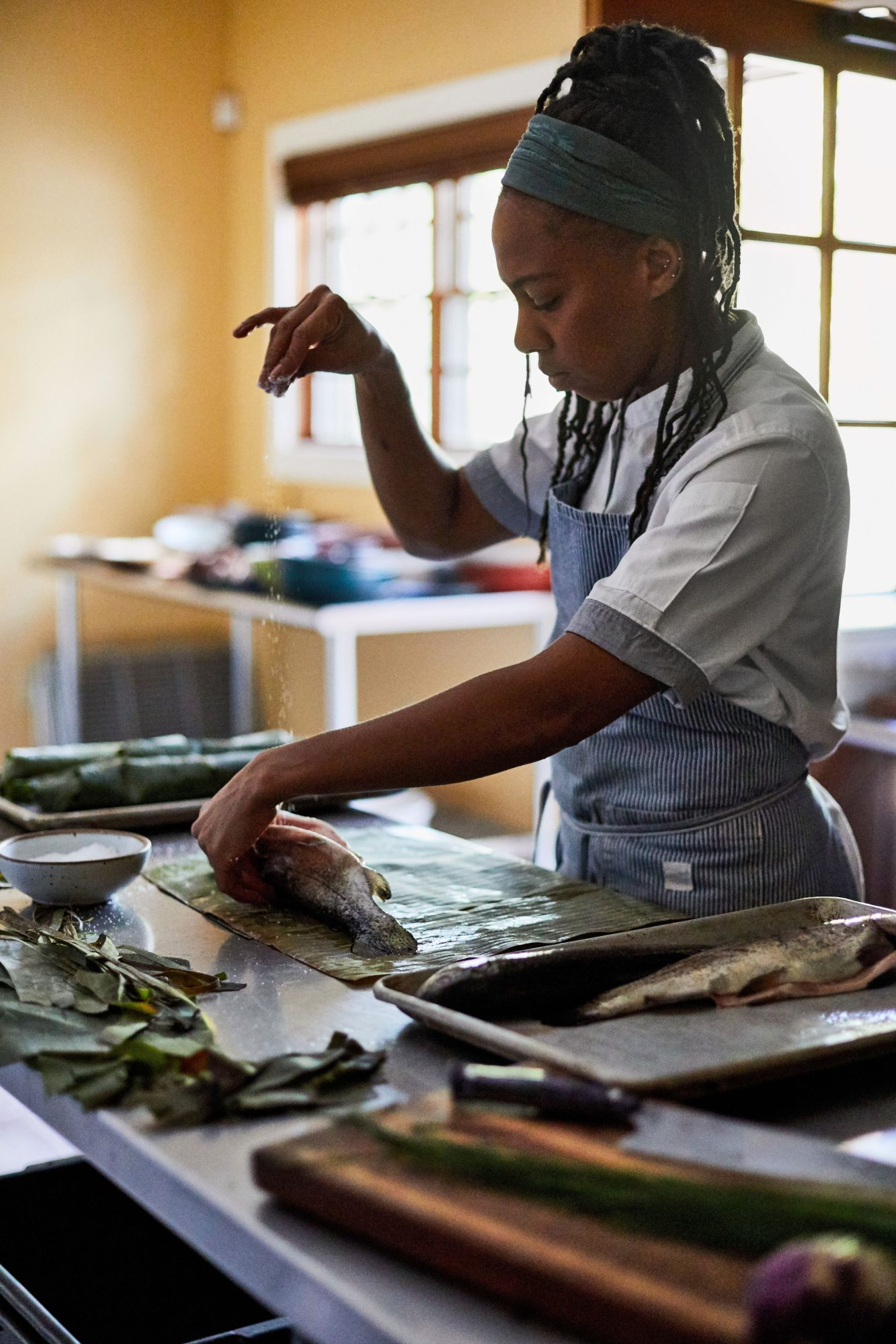 Chef Ashleigh Shanti seasoning trout before wrapping and cooking it in plantain leaves