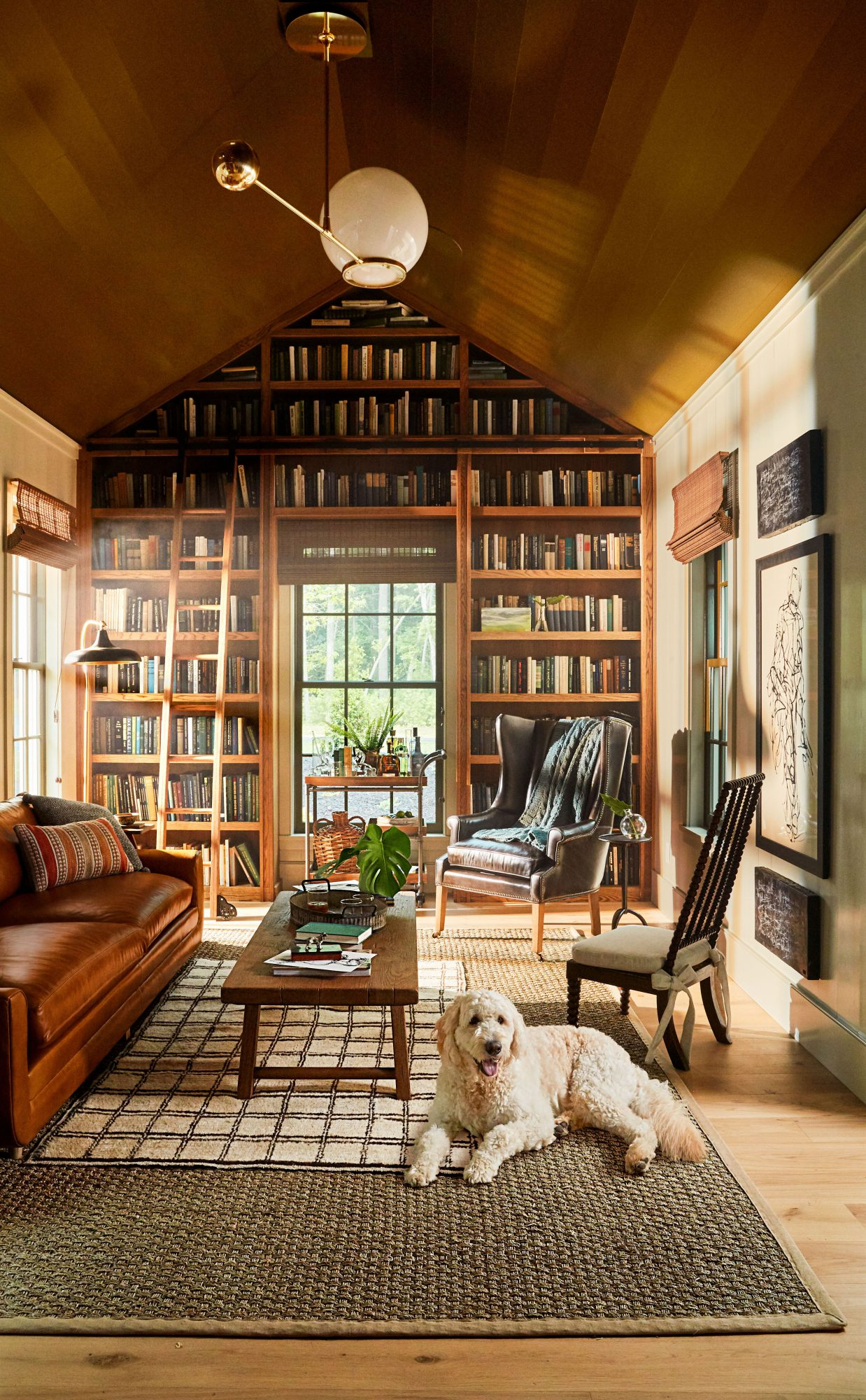 Idea House 2020 Library with Bookshelf Wall, Leather Sofa, and Dark Painted Ceiling