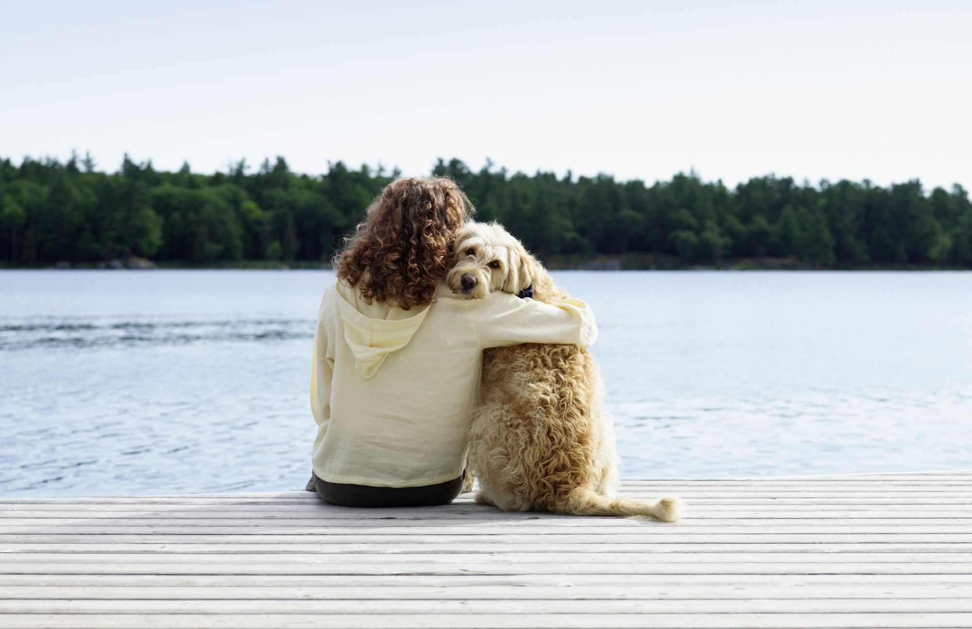 Woman Sitting on Dock with Dog