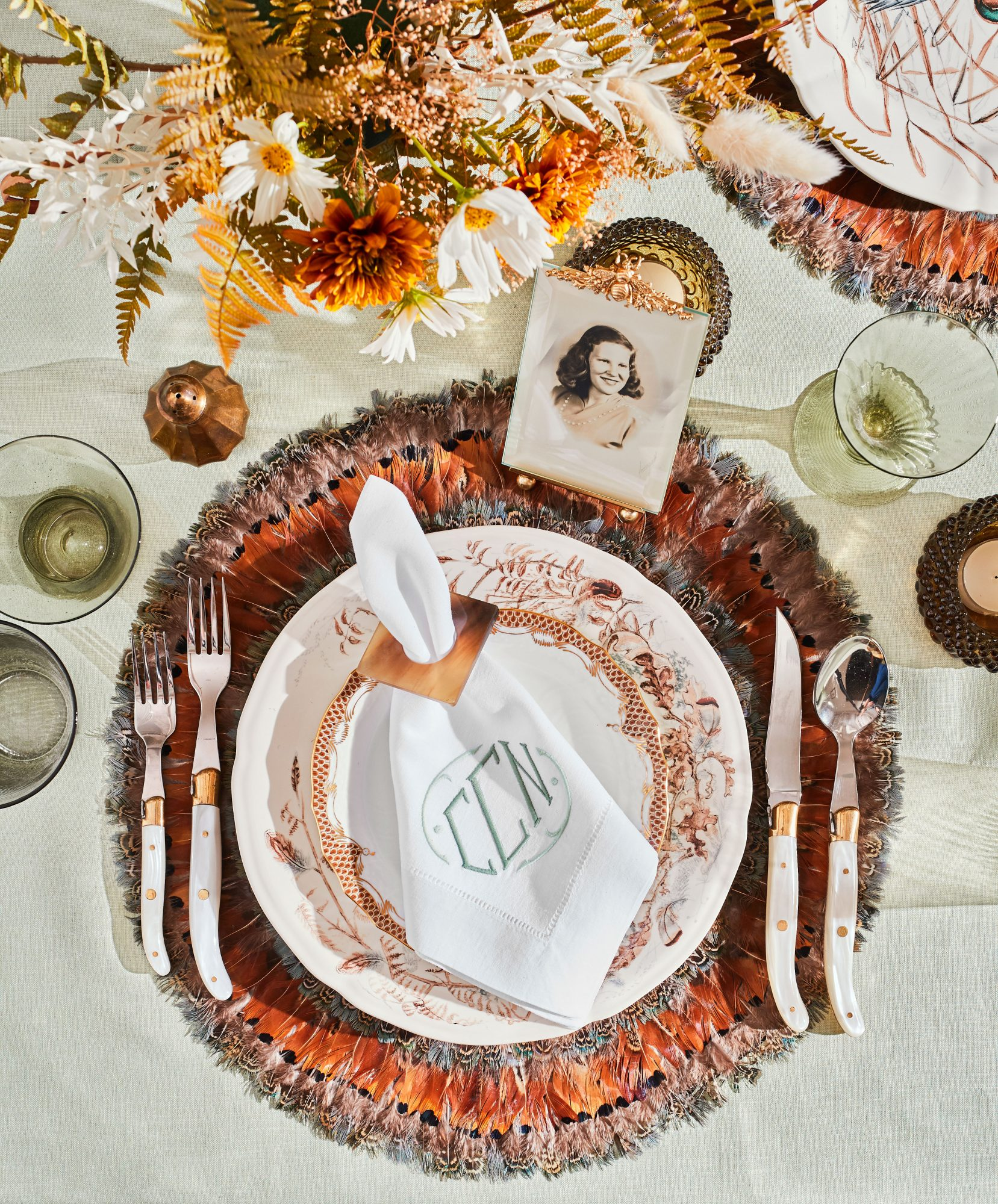 Thanksgiving Table Setting with Feathered Placemats, Monogrammed Napkins, and Photos as Place Cards