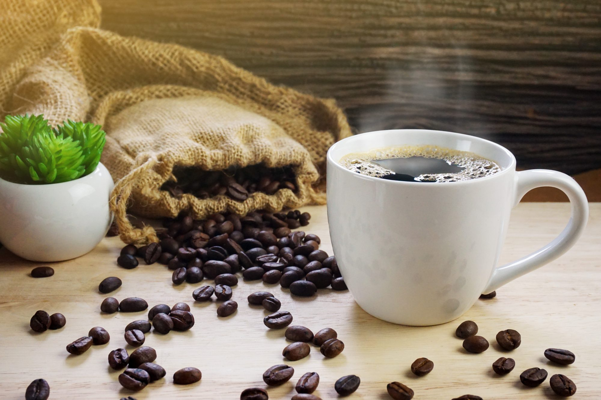 Close-Up Of Drink In Cup With Roasted Coffee Beans On Table