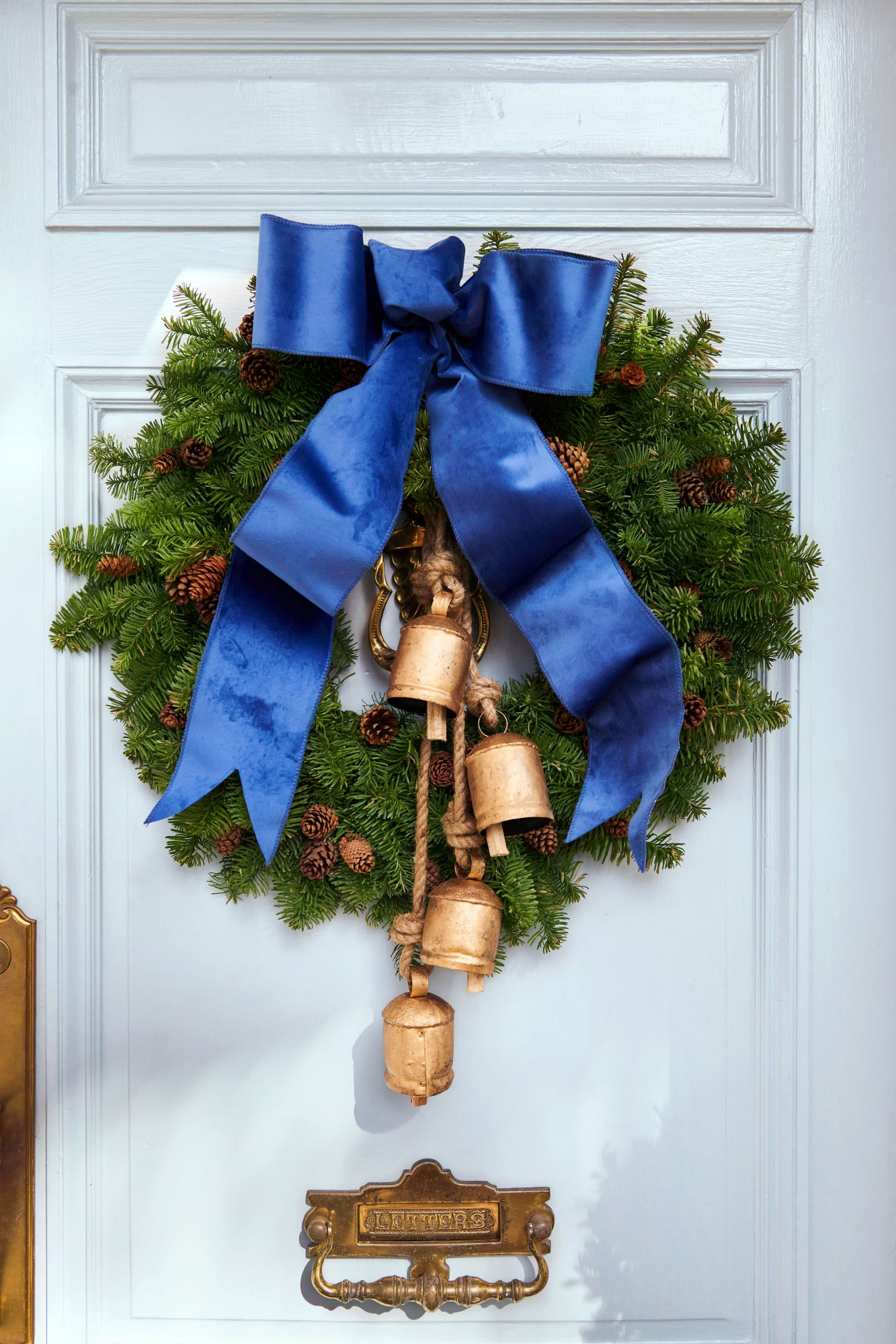 Blue front door with Christmas wreath with blue ribbon, pinecones, and bells