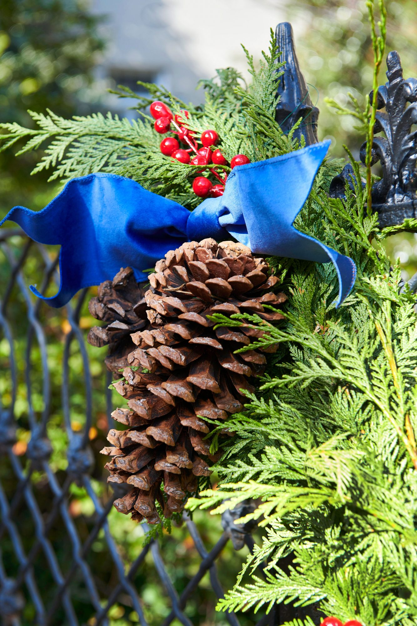Pinecones with berries and blue ribbon on greenery swag