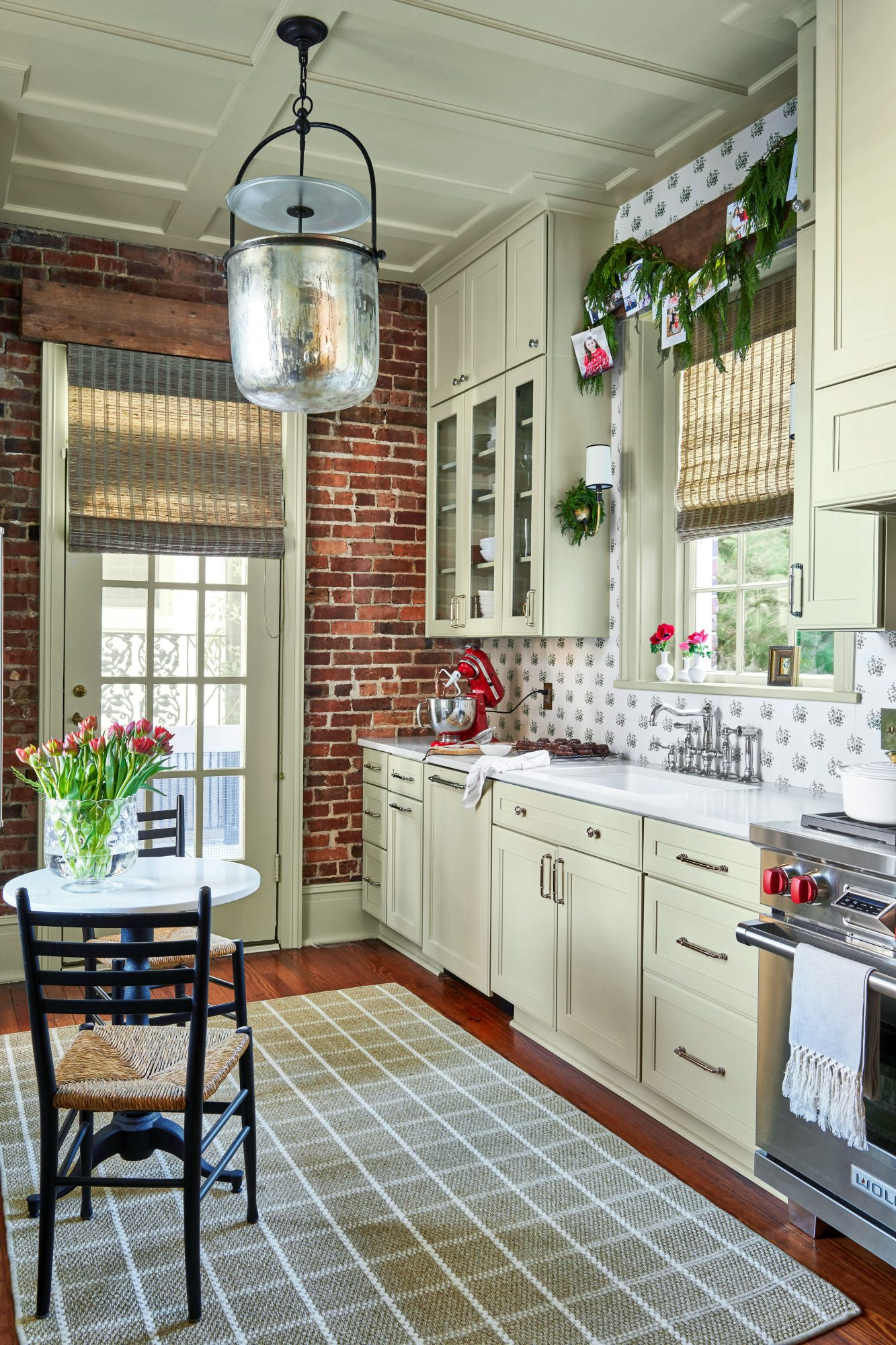 Galley kitchen with light green cabinetry and exposed brick wall