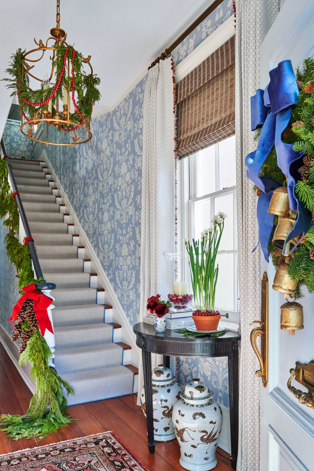 Blue and white foyer decorated for Christmas with greenery and red and blue ribbons
