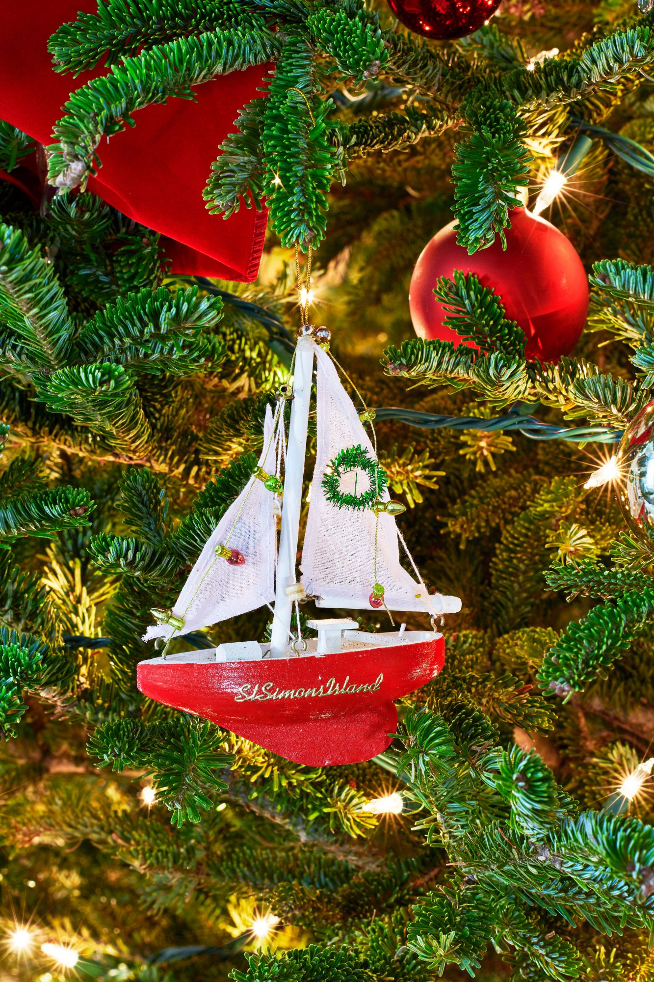Red sailboat ornament on Christmas tree