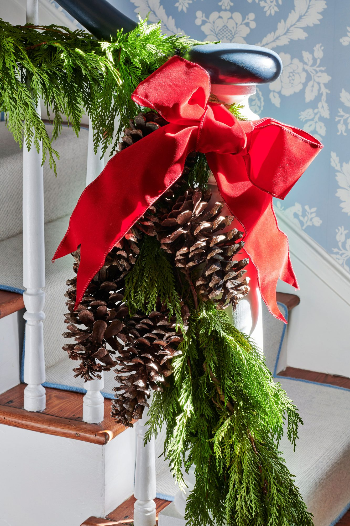Banister greenery swag with red bow and pinecones