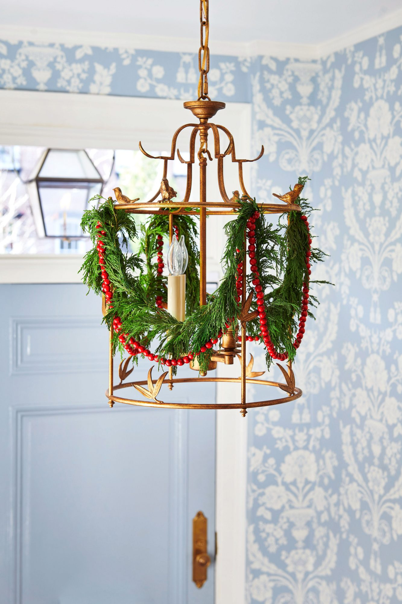 Foyer light fixture draped in greenery and cranberries