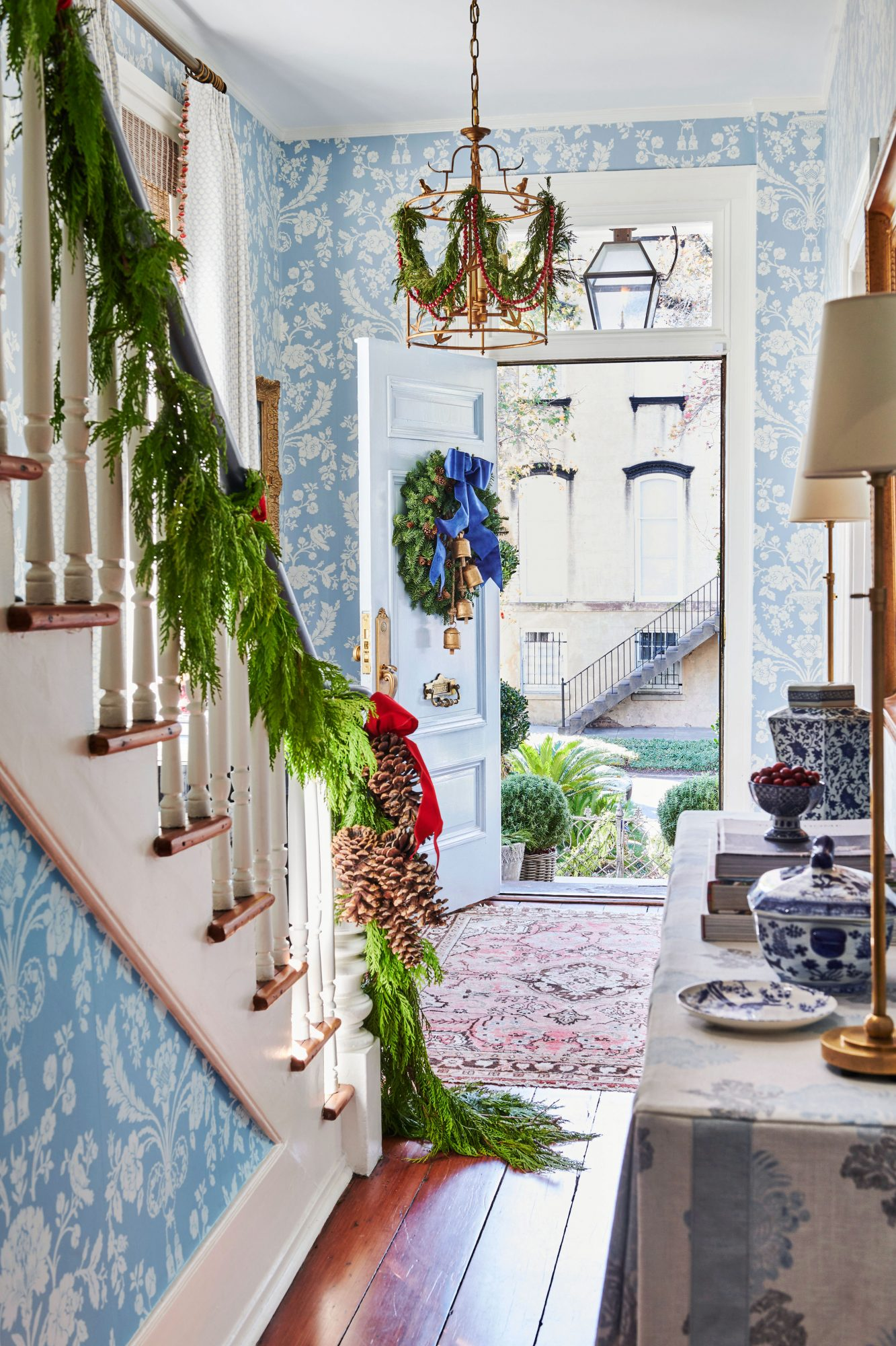 Blue and White wallpapered foyer with stairs draped in greenery for Christmas