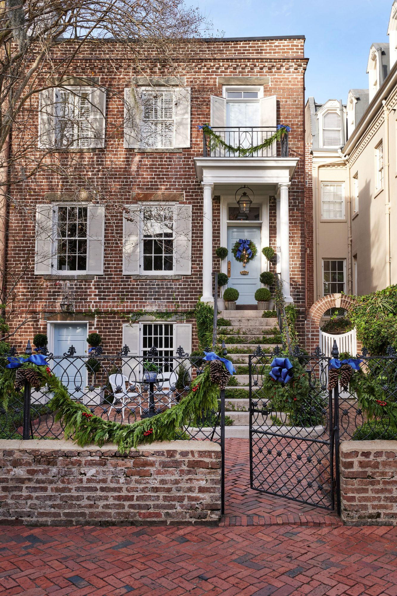 Historic Savannah brick home decorated for Christmas with greenery and blue ribbons