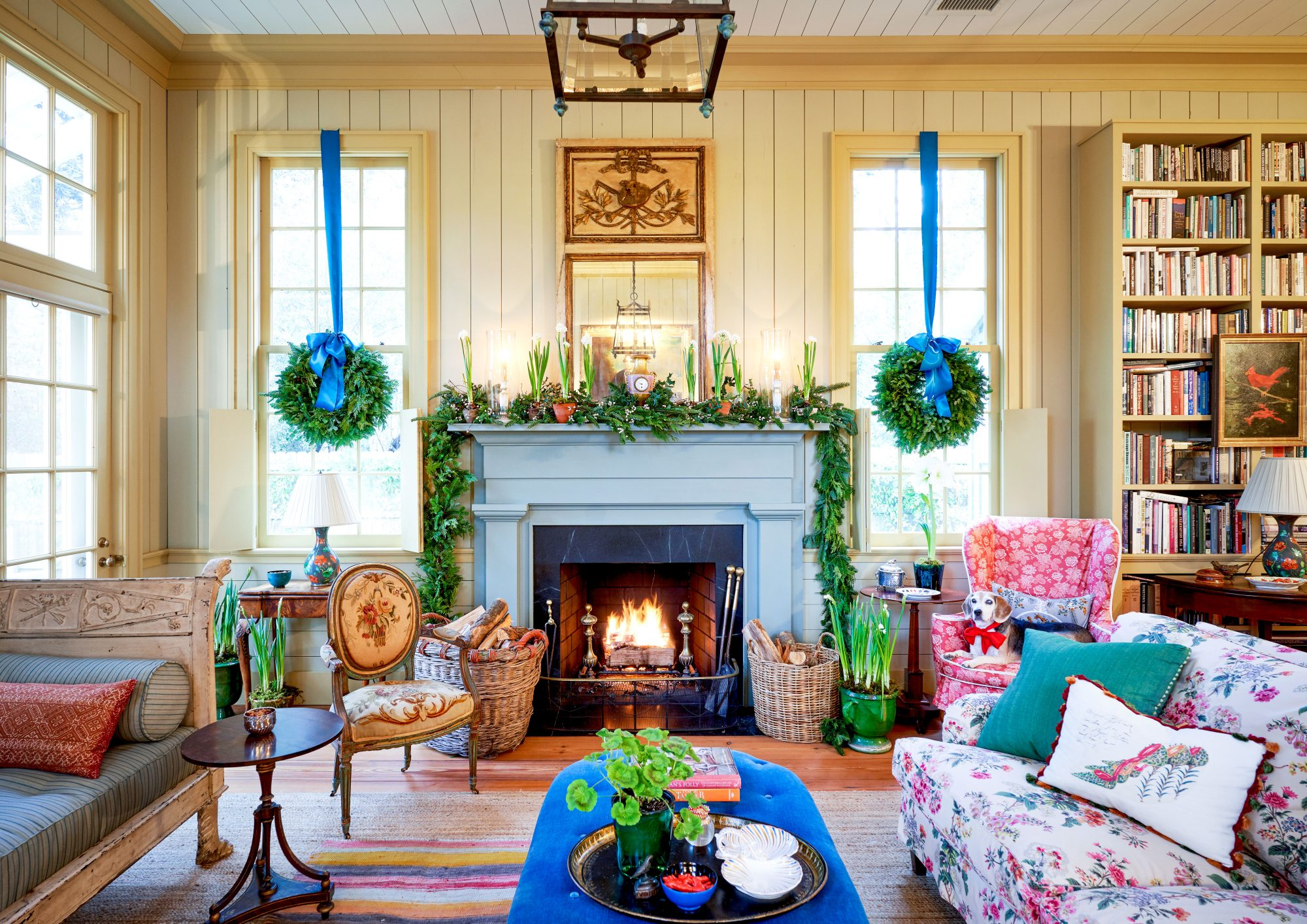 Living Room decorated for Christmas with wreaths in the windows and garland on the mantel