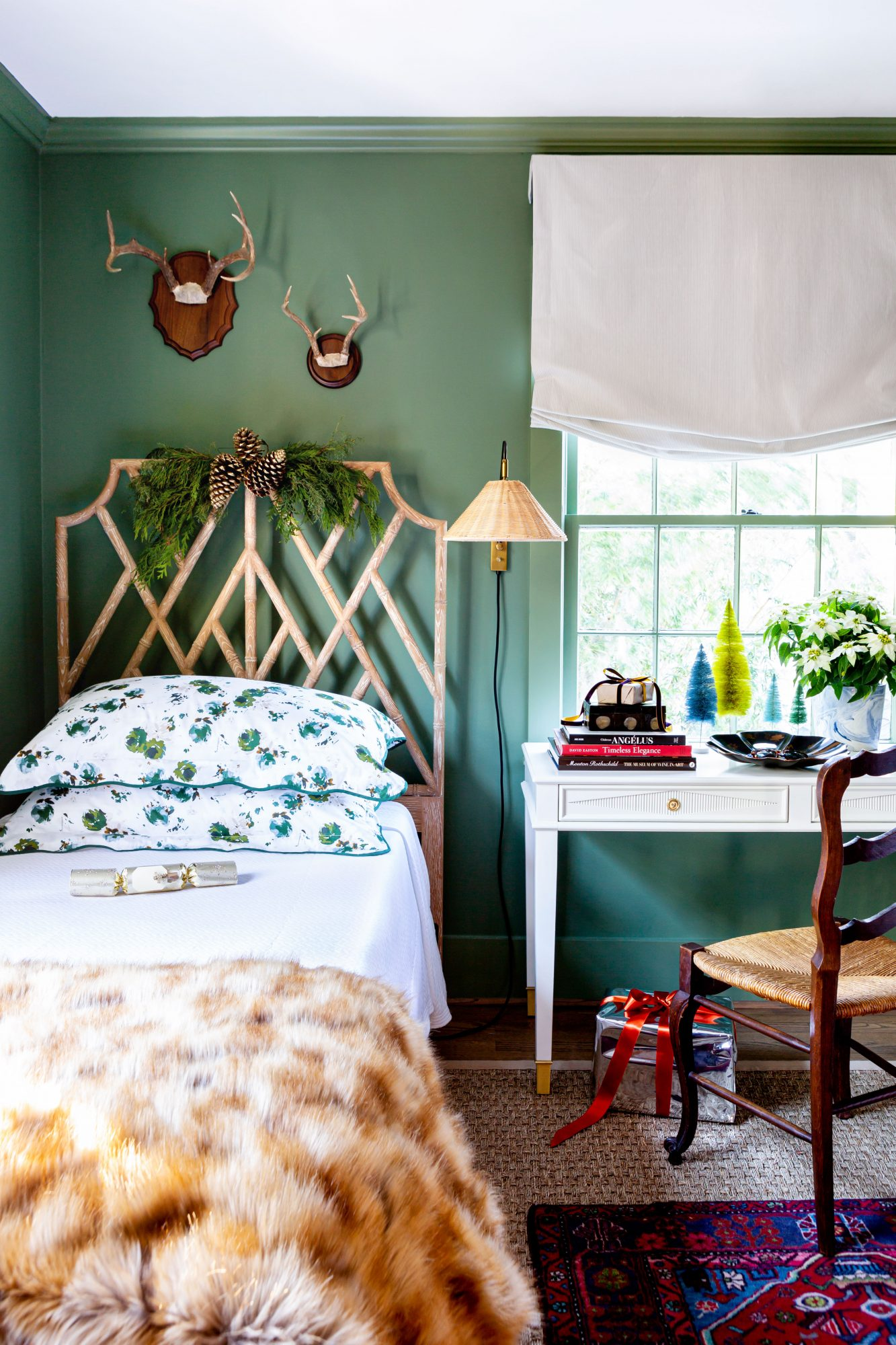 Green guest room with twin beds decorated for Christmas with greenery and bottle brush trees.
