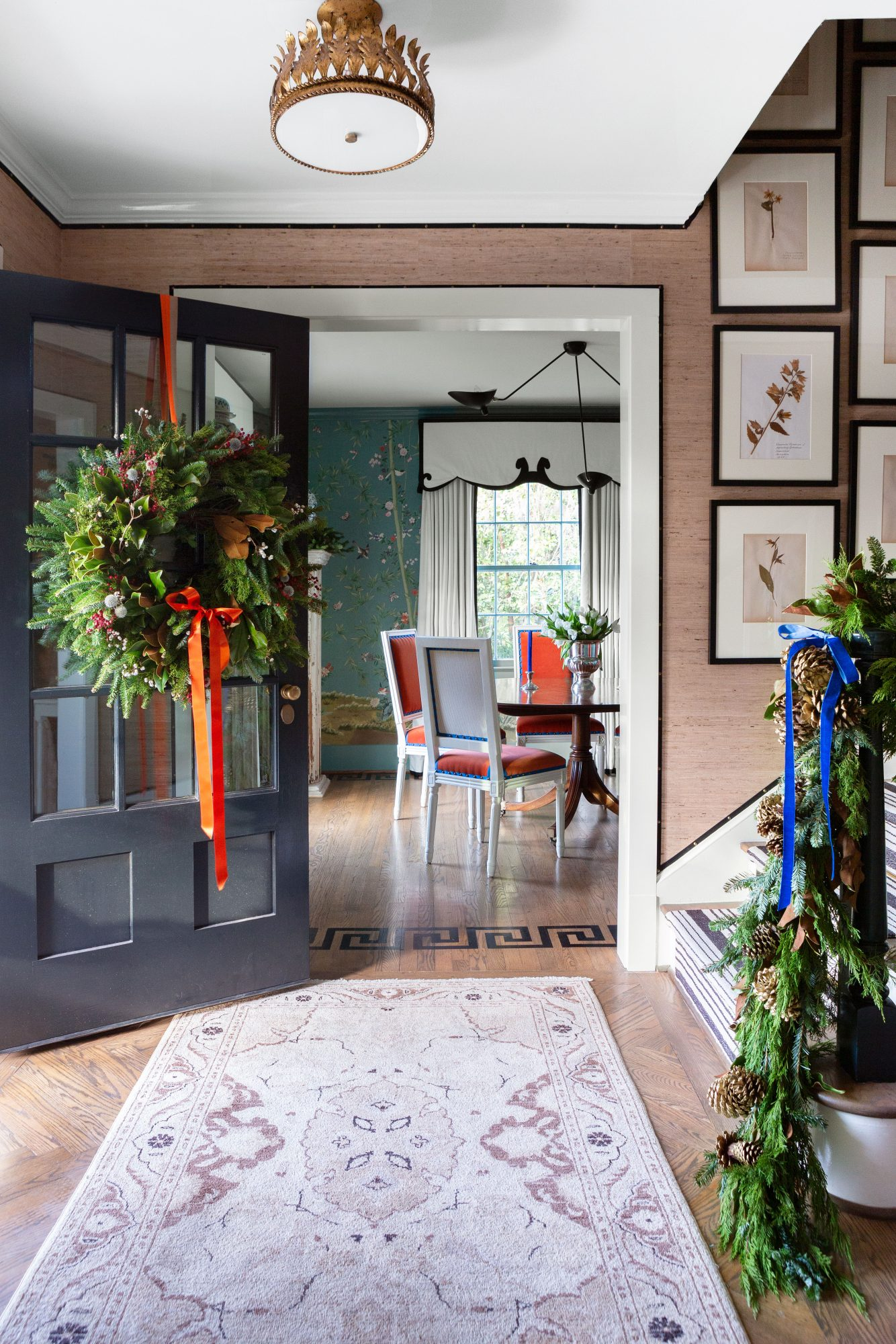 Entry with dark door opened to show large wreath and garland draped on the banister.