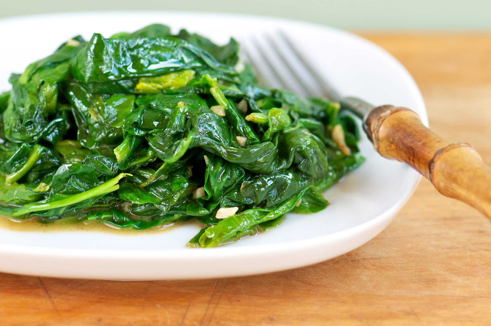 White Plate of Fresh Sauteed Spinach with Garlic on Wood