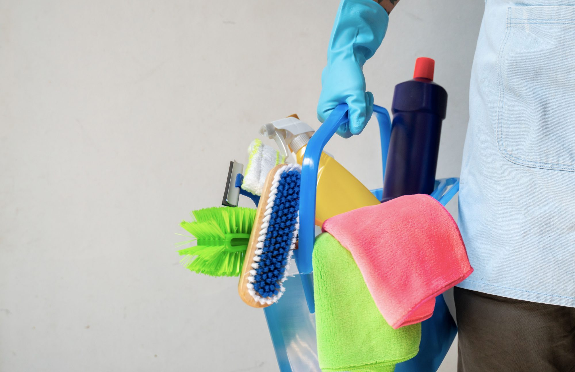 Gloved Hand Holding Cleaning Supplies