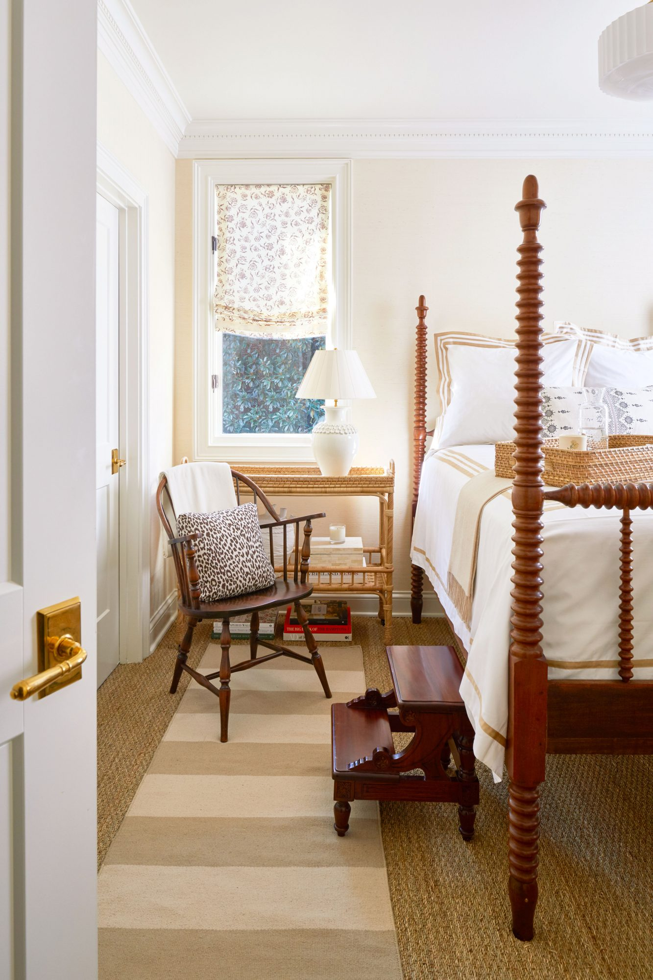 Welcoming guest room with four-poster spool bed and crisp white bedding