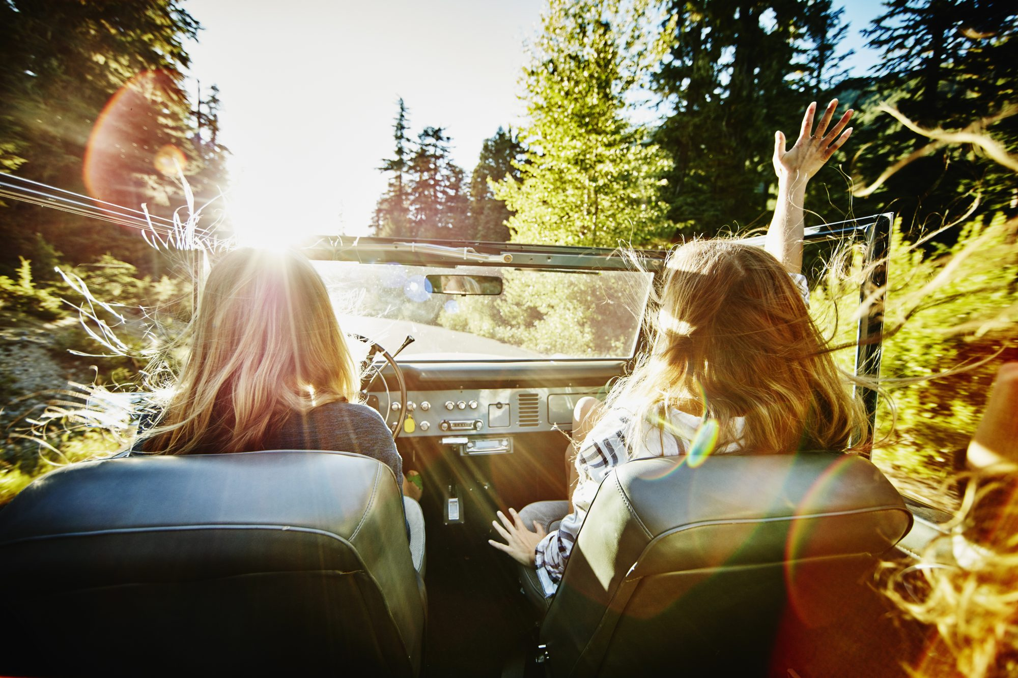 Friends riding in convertible on summer evening